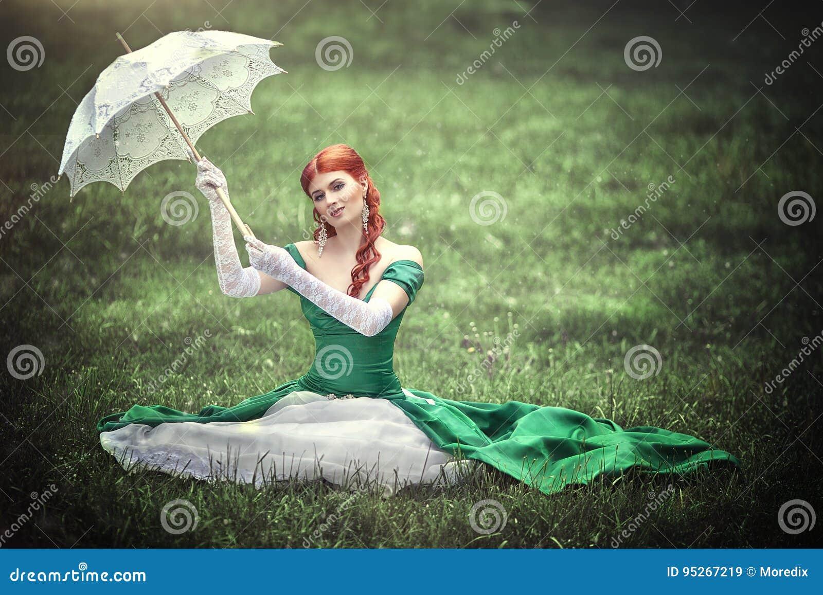 Mooi jong roodharig meisje in een middeleeuwse groene kleding met een parapluzitting op het gras