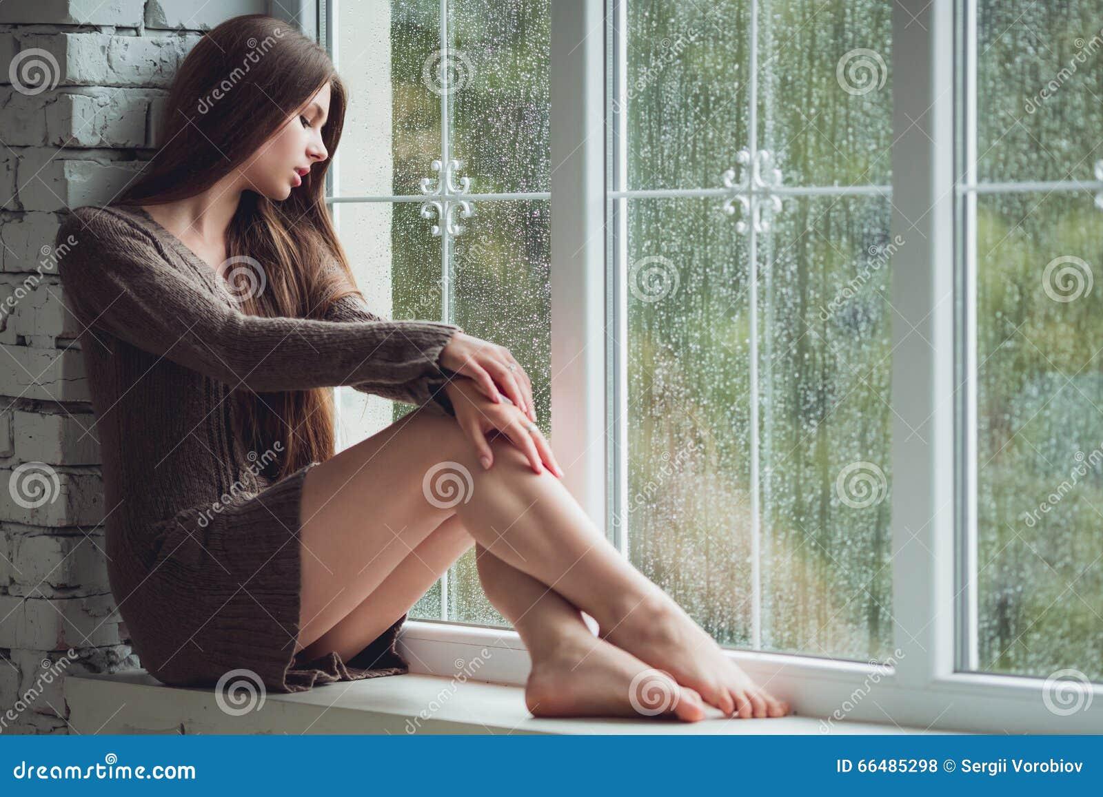 Mooi jong vrouw het zitten alleen dichtbijgelegen venster met regendalingen Sexy en droevig meisje Concept eenzaamheid
