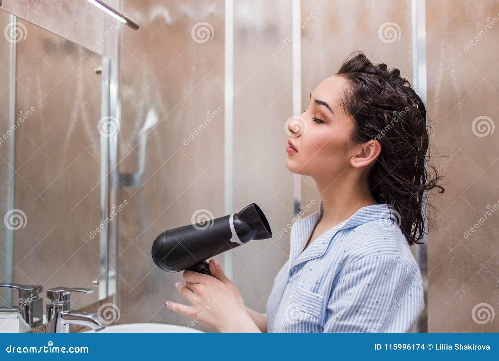 Mooi jong vrouwen drogend haar na douche in lichte badkamers thuis