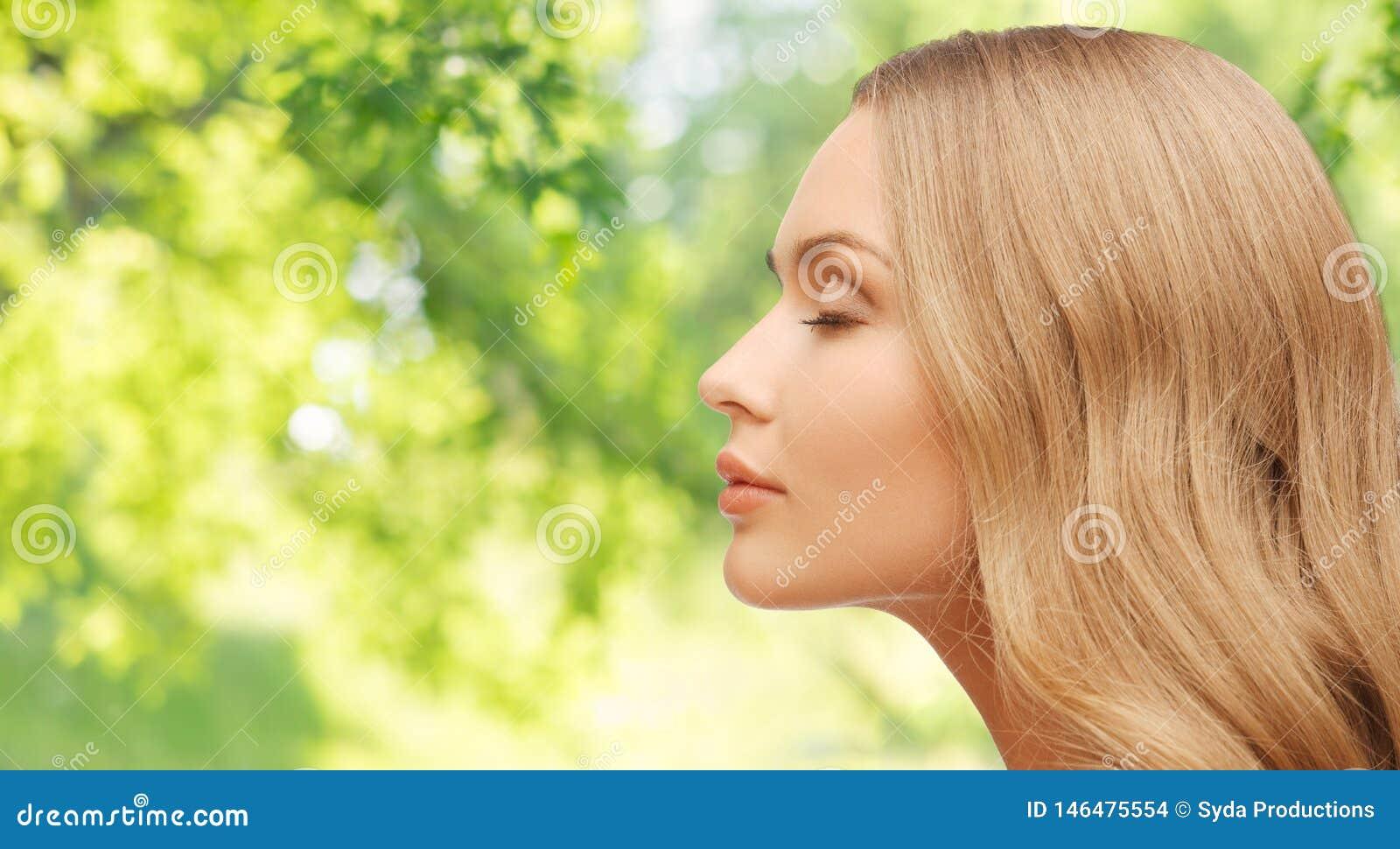 Mooi jong vrouwengezicht over natuurlijke achtergrond