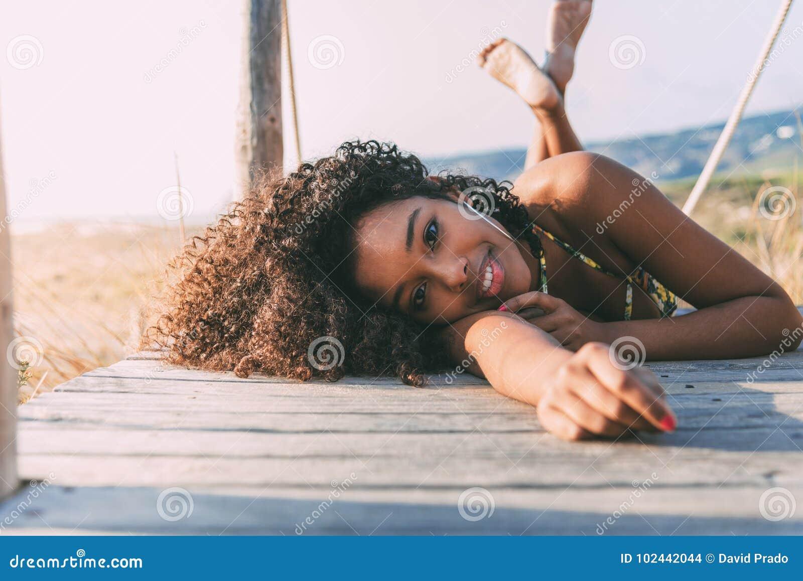 Mooi jong zwarte die in een houten voetbrug liggen