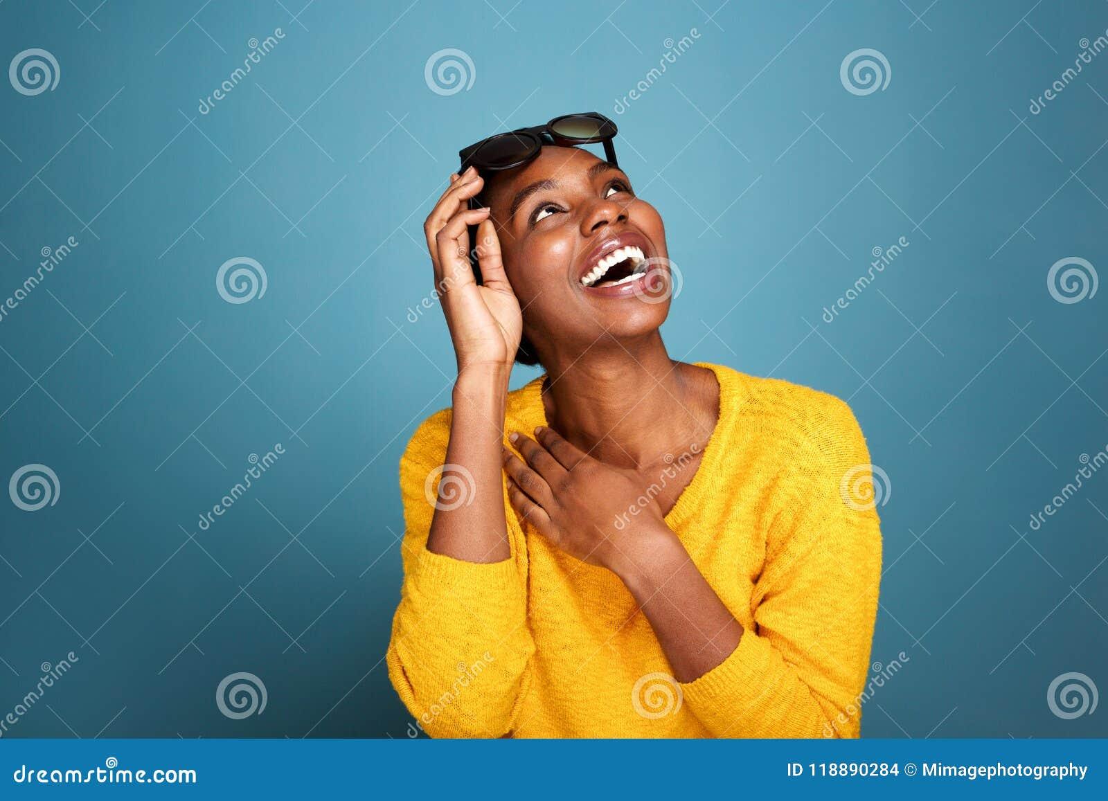 Mooi jong zwarte die in zonnebril door blauwe muur lachen