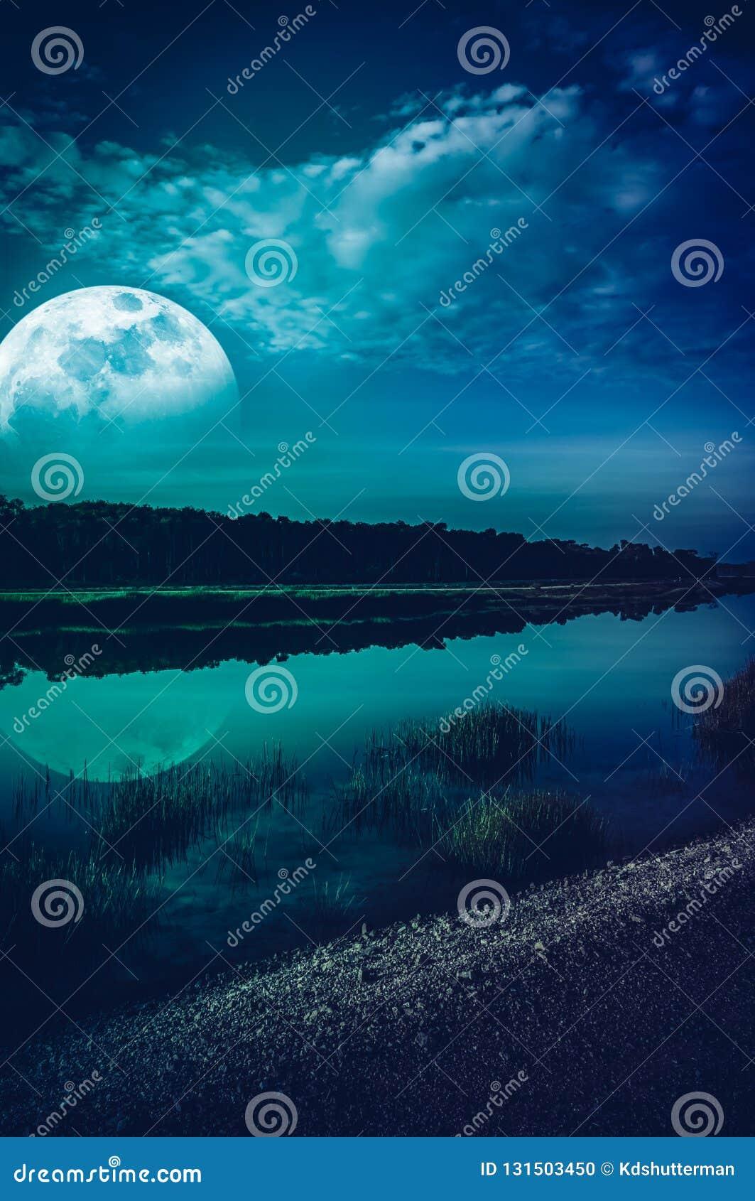 Mooi landschap van blauwe hemel met wolk en super maan boven silhouetten van bomen bij rivieroever De achtergrond van de serenite