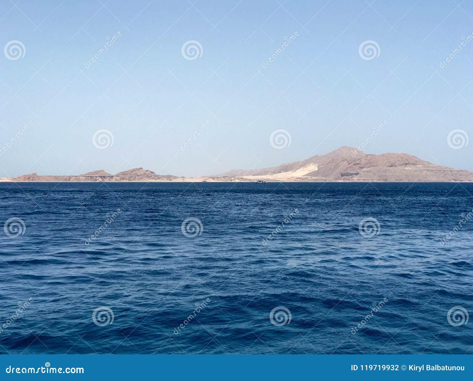 Mooi landschap van het blauwe zoute overzees en het verre hooggebergte