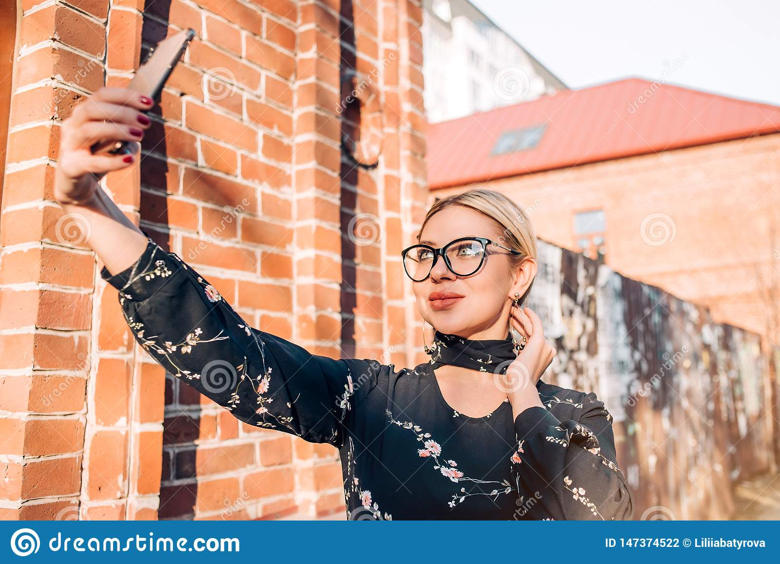 Mooi leuk blondemodel in kleding het stellen in de stad