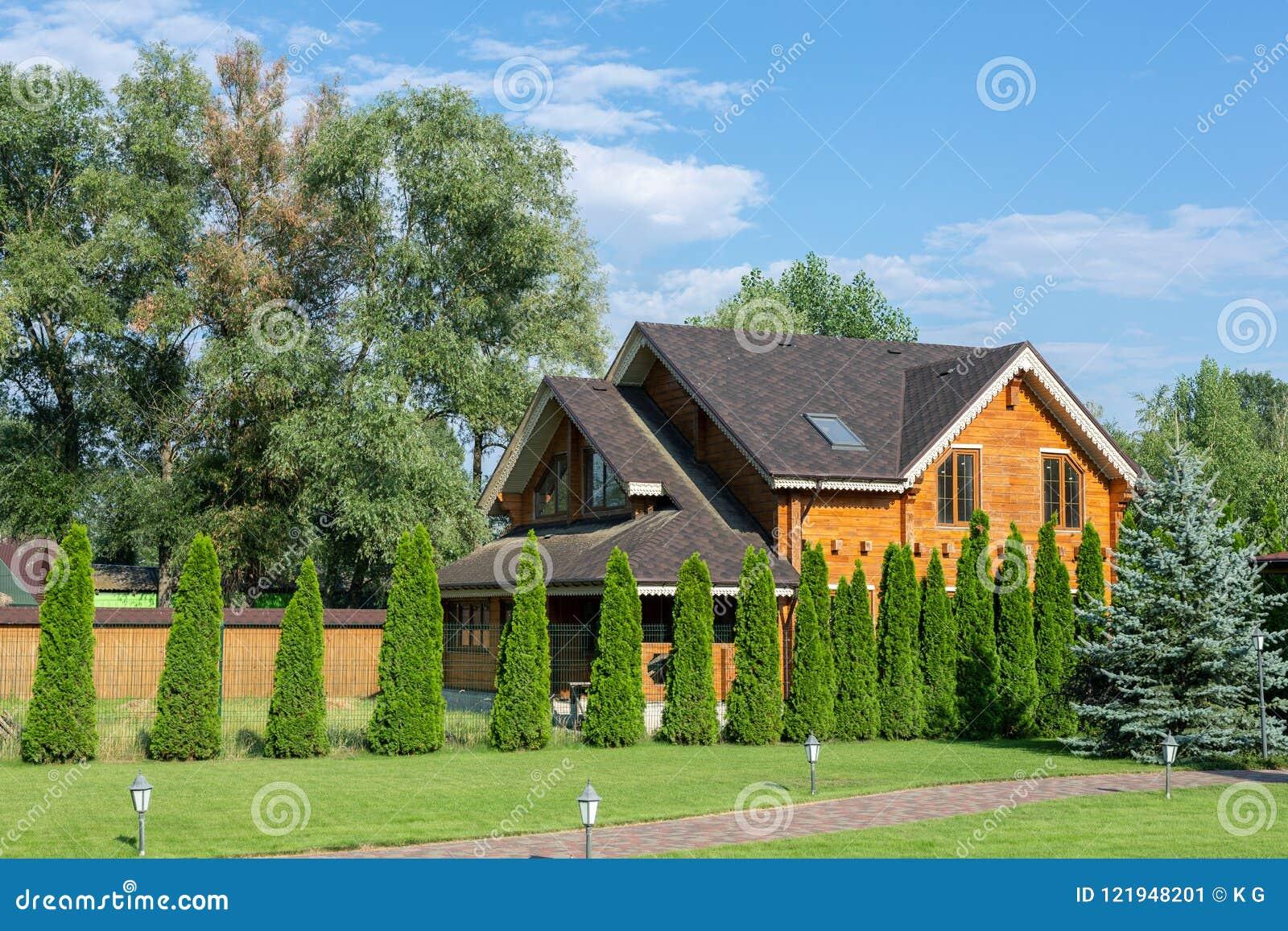 Mooi luxe groot blokhuis De villa van het houtplattelandshuisje met met groen gazon, tuin en blauwe hemel op achtergrond