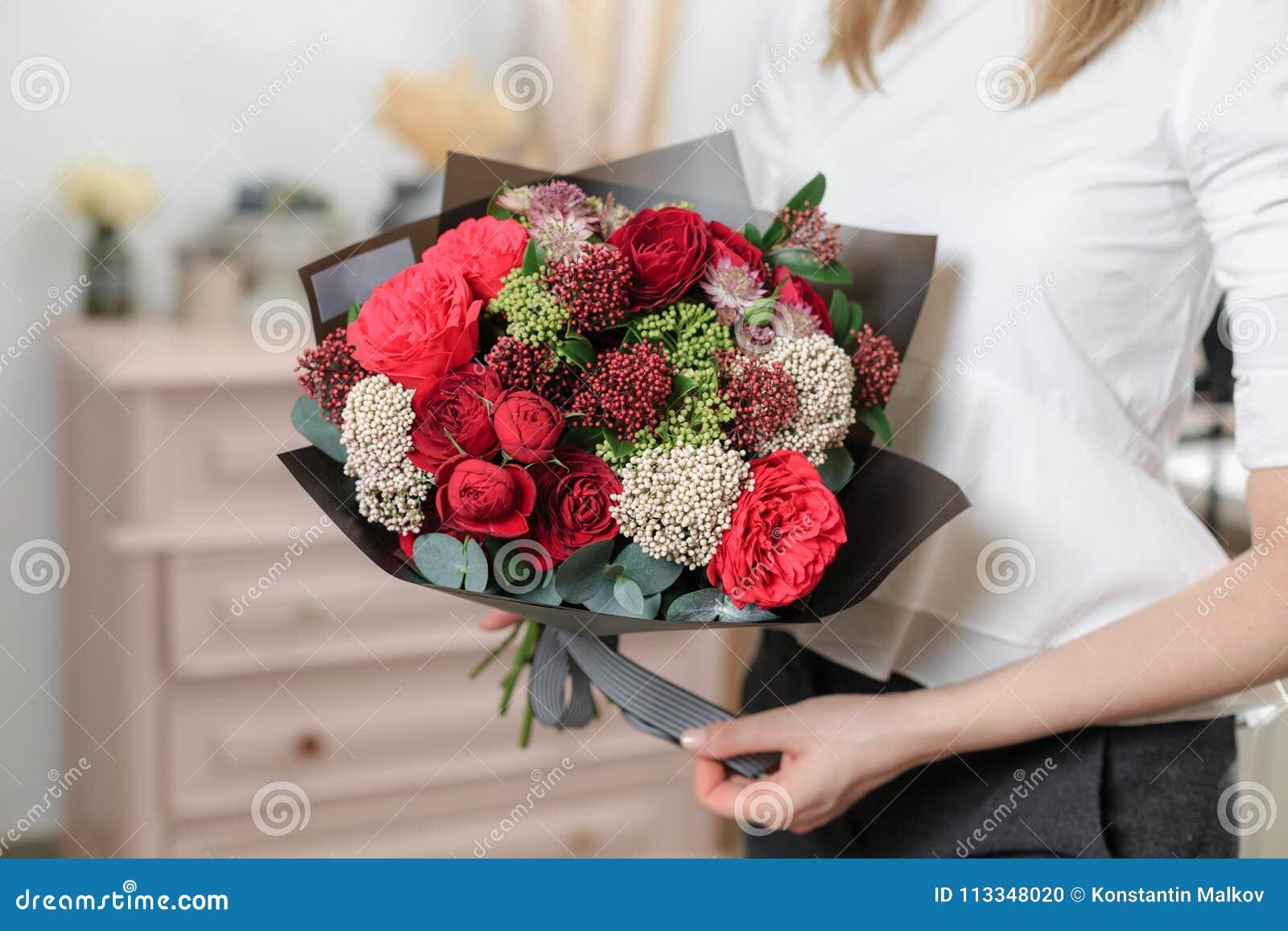 Mooi luxeboeket van gemengde bloemen in vrouwenhand het werk van de bloemist bij een bloemwinkel Een kleine familie
