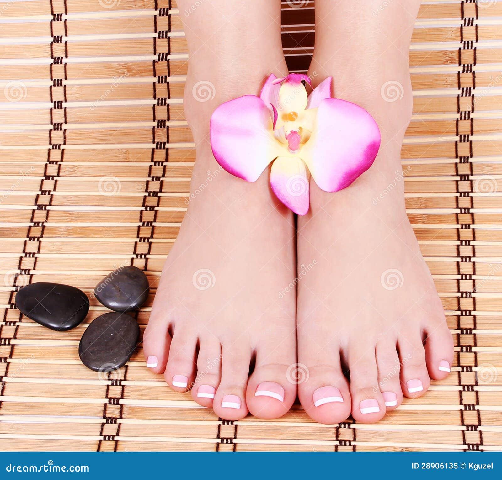 Mooi manicured vrouwelijke naakte voeten met orchideebloemen en kuuroordstenen over bamboemat