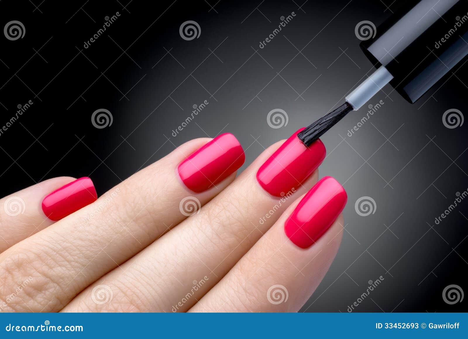Mooi manicureproces. Nagellak die worden het toegepast om te overhandigen, poetsmiddel is een roze kleur.