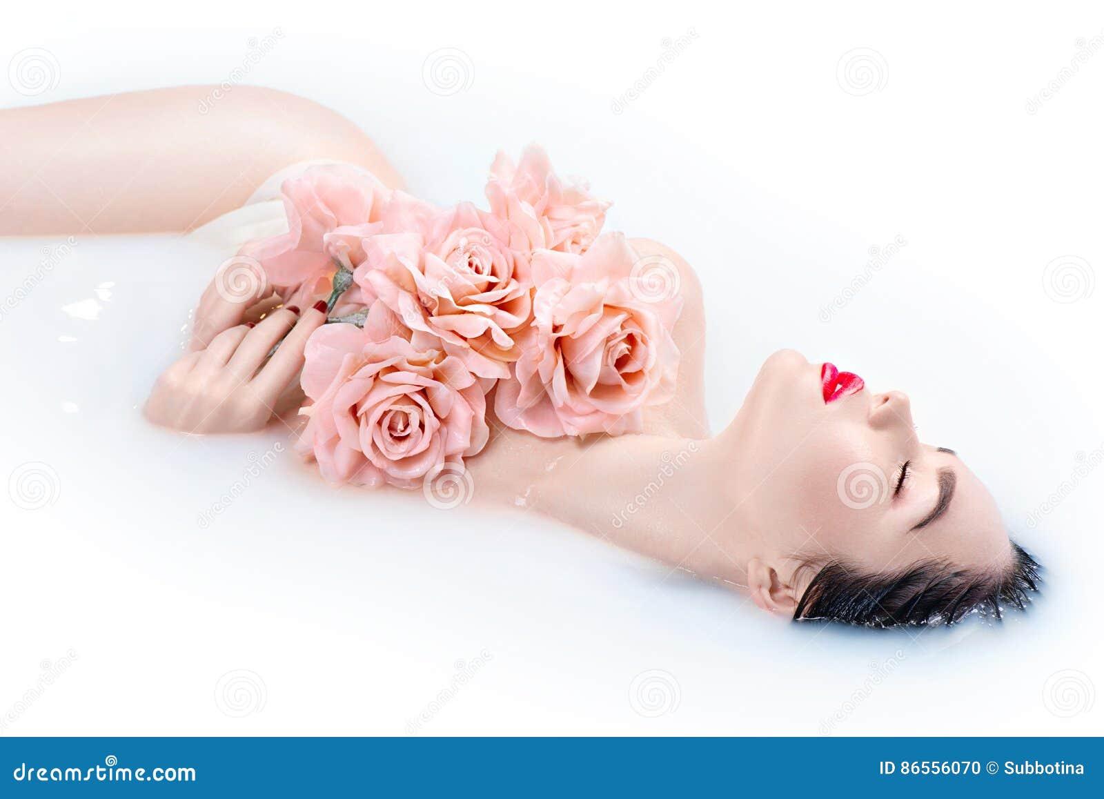 Mooi Mannequinmeisje met heldere make-up en roze rozen die melkbad nemen