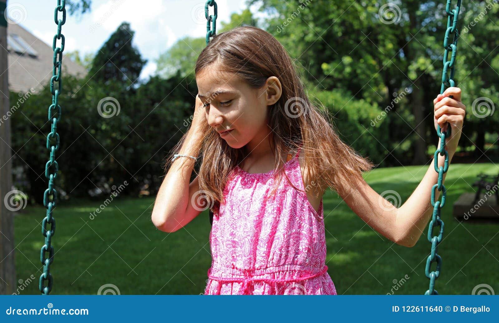 Mooi meisje bij schommeling in het park met roze kleding tijdens de zomer in Michigan