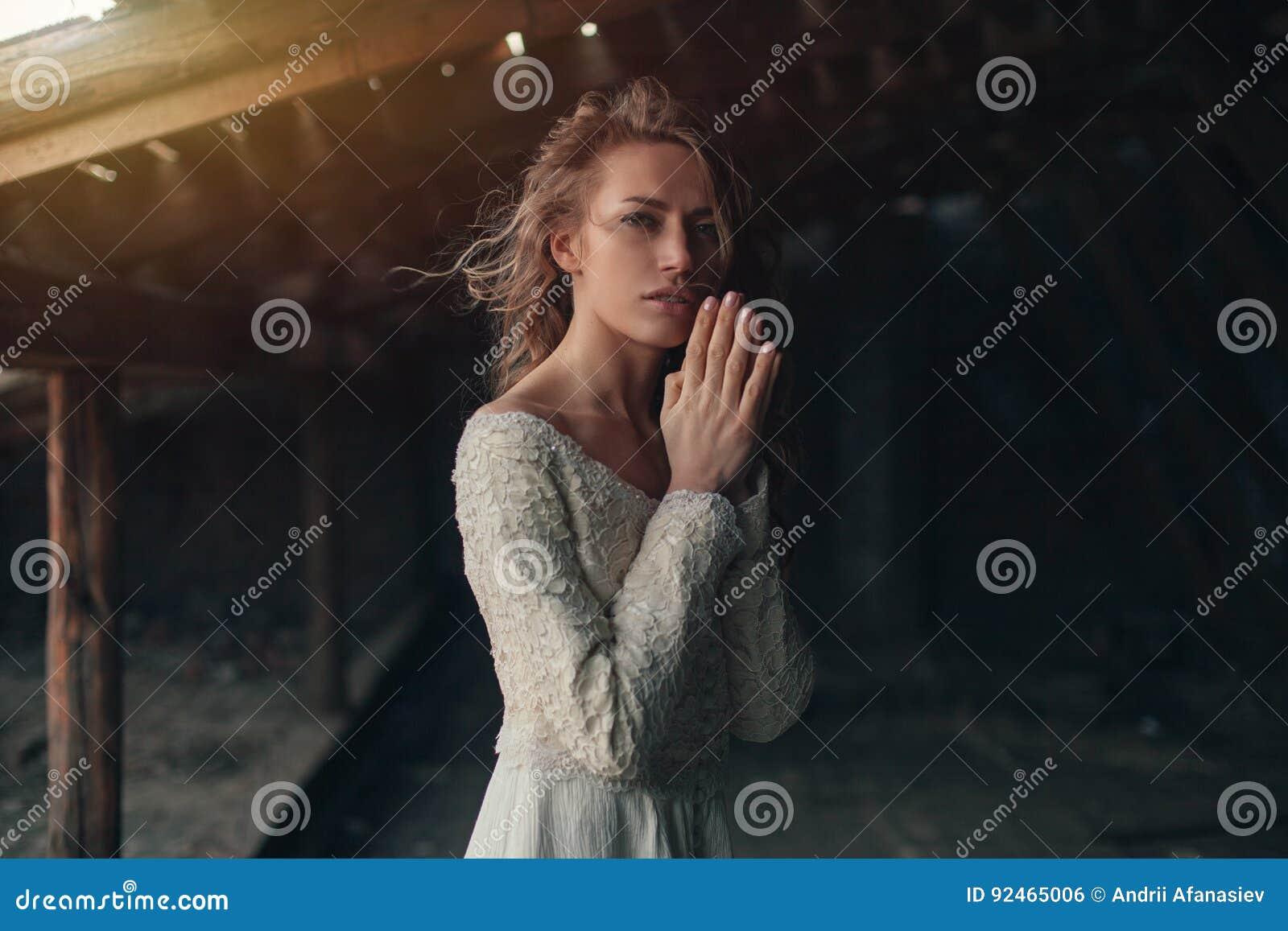 Mooi meisje binnen in witte uitstekende kleding met het krullende haar stellen op de zolder Vrouw in retro kleding Ongerust gemaa