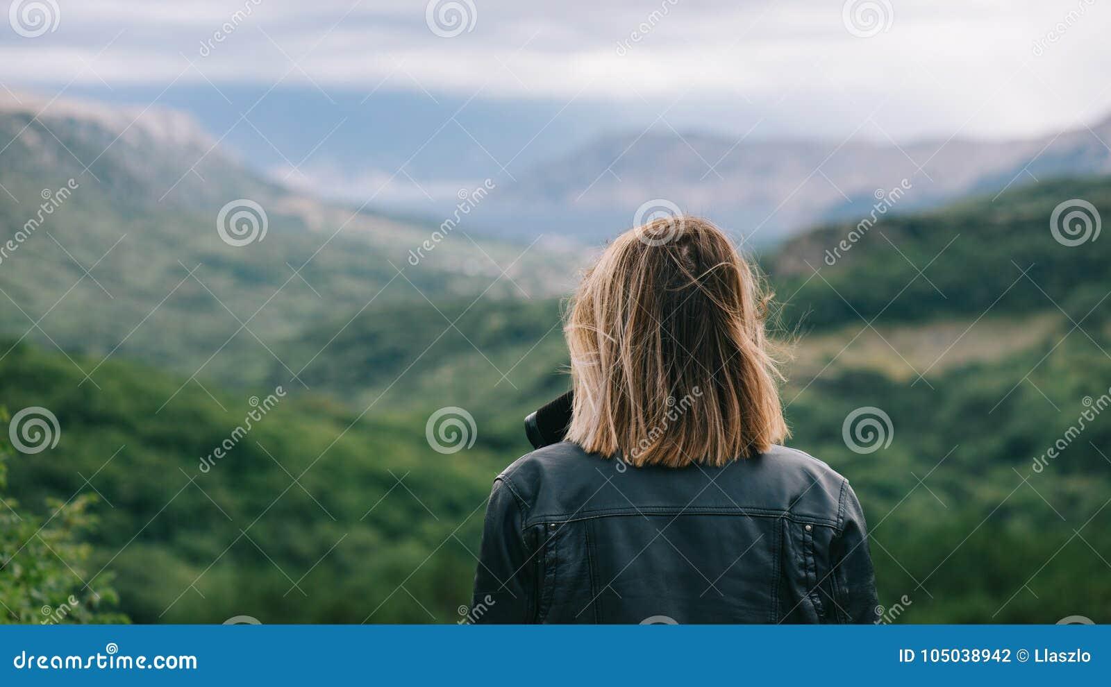 Mooi meisje bovenop berg het letten op landschap