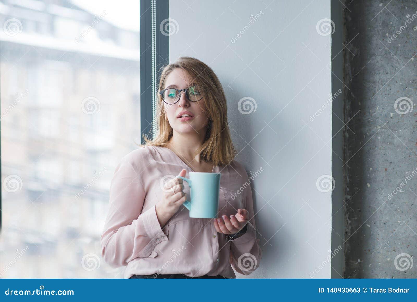 Mooi meisje in de glazentribunes in de muur dichtbij het venster met een kop van koffie