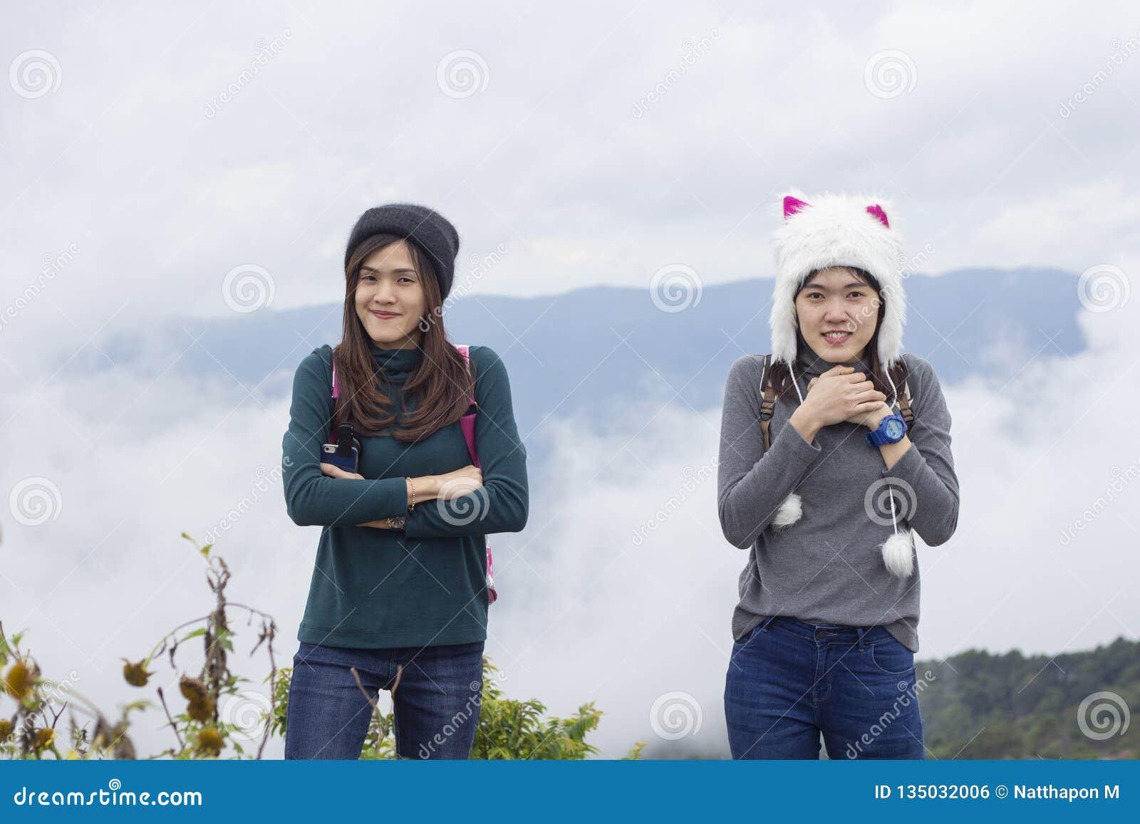 Mooi meisje in de winterhoed op een achtergrond van overzees van mistmeisje in een hoed op de achtergrond van bergen