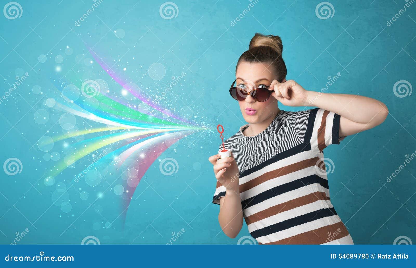 Mooi meisje die abstracte kleurrijke bellen en lijnen blazen
