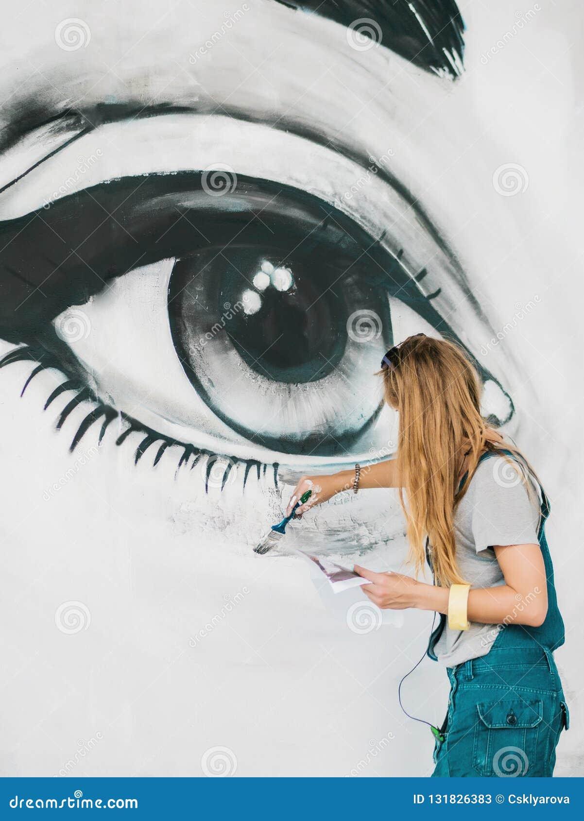 Mooi meisje die graffiti van groot vrouwelijk gezicht met aërosolnevel maken op stedelijke straatmuur Creatief art begaafd