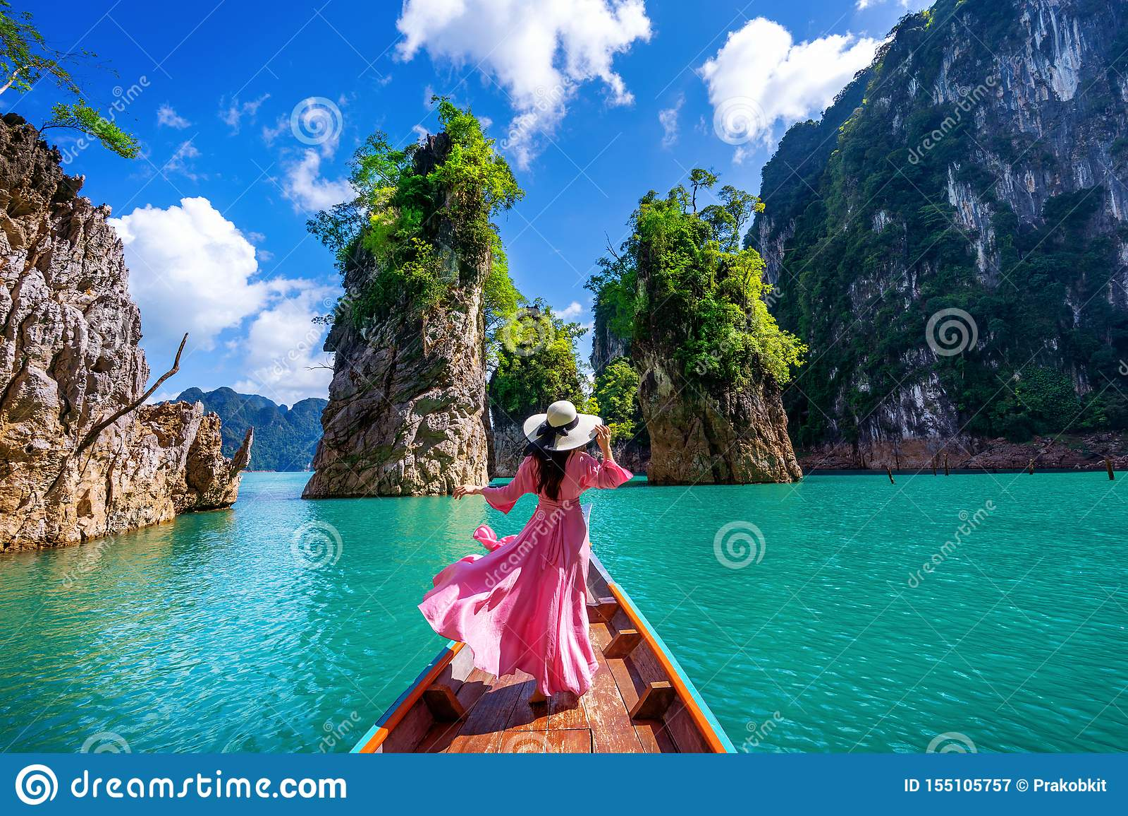 Mooi meisje die zich op de boot bevinden en aan bergen in Ratchaprapha-Dam kijken