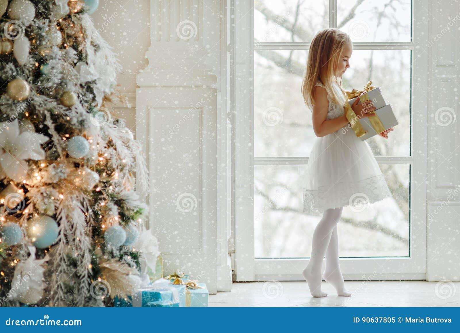 Mooi meisje die zich op tiptoe bij het grote venster bevinden