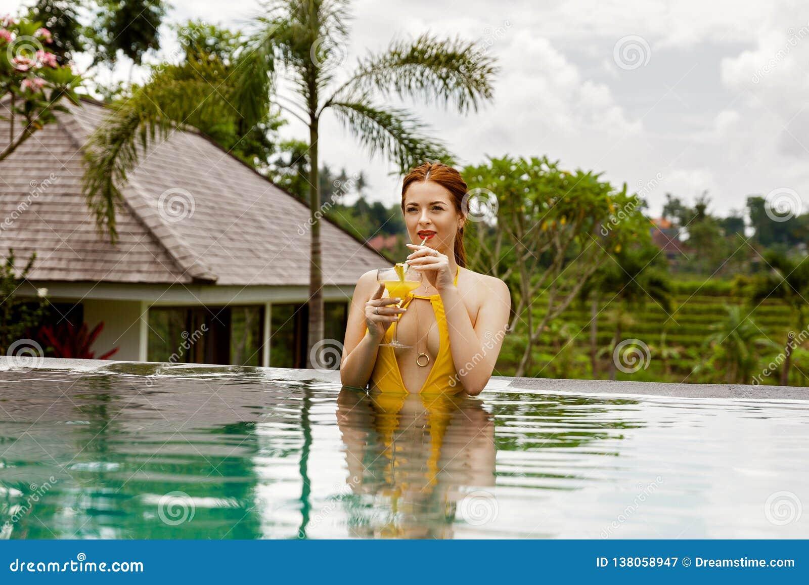 Mooi meisje in een geel zwempak in het zwembad