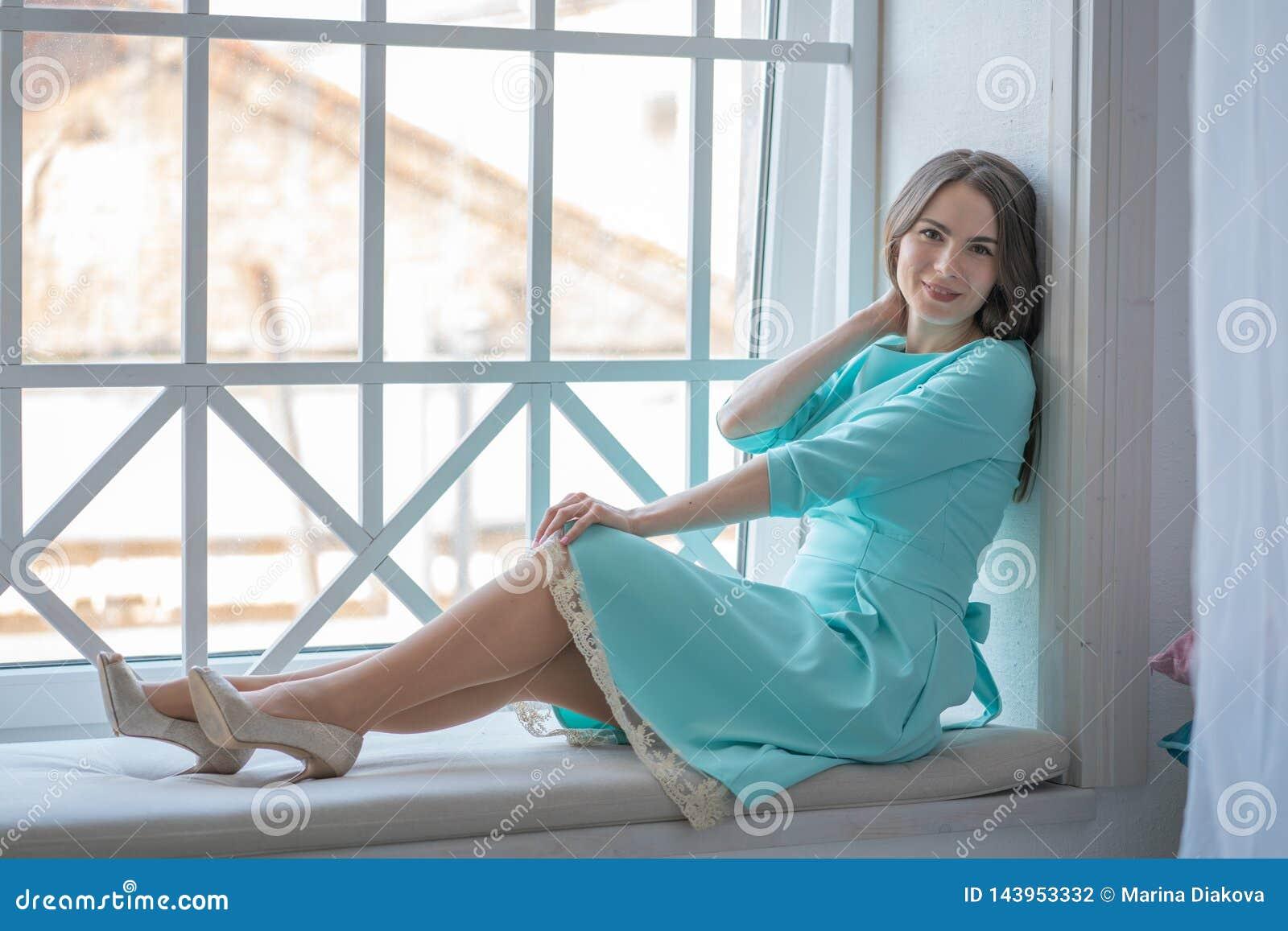 Mooi meisje in een leuke kledingszitting op de vensterbank door het venster in de middag