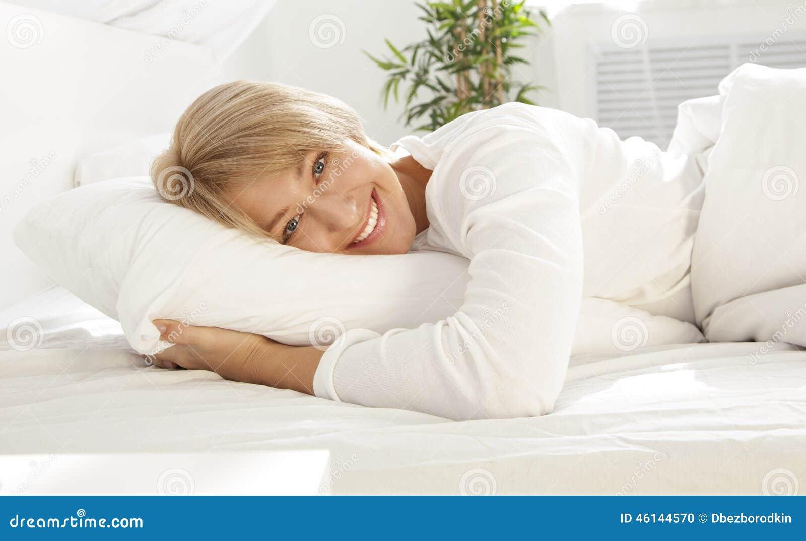 Mooi meisje in een wit bed in de ochtend, het glimlachen
