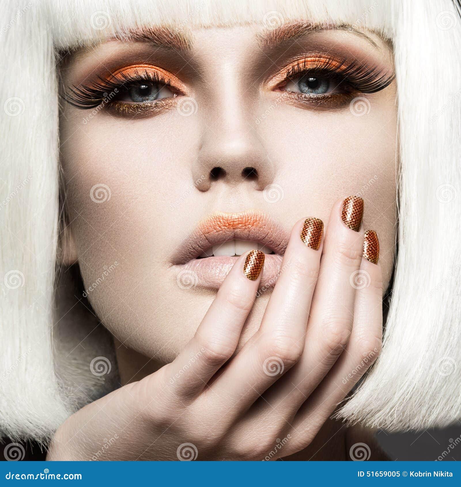 Mooi meisje in een witte pruik, met gouden make-up en spijkers Feestbeeld Het Gezicht van de schoonheid