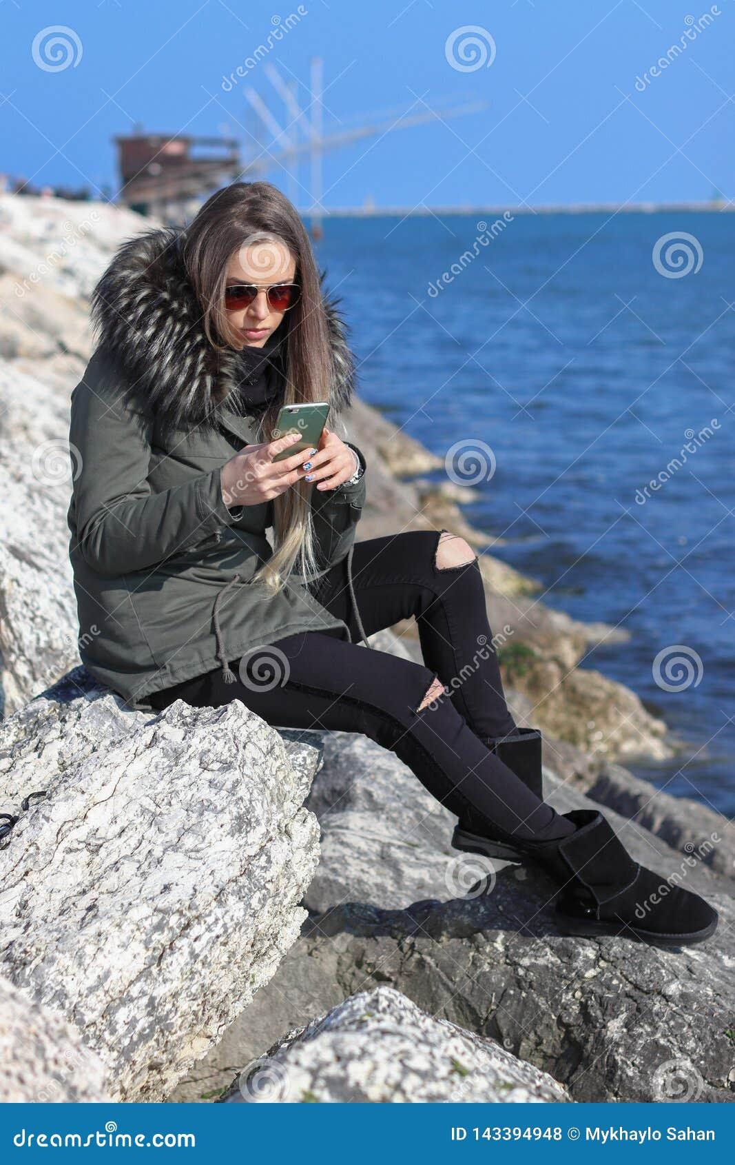 Mooi meisje Gelukkige vrouw die aan de telefoon op het strand met het overzees op de achtergrond kijken