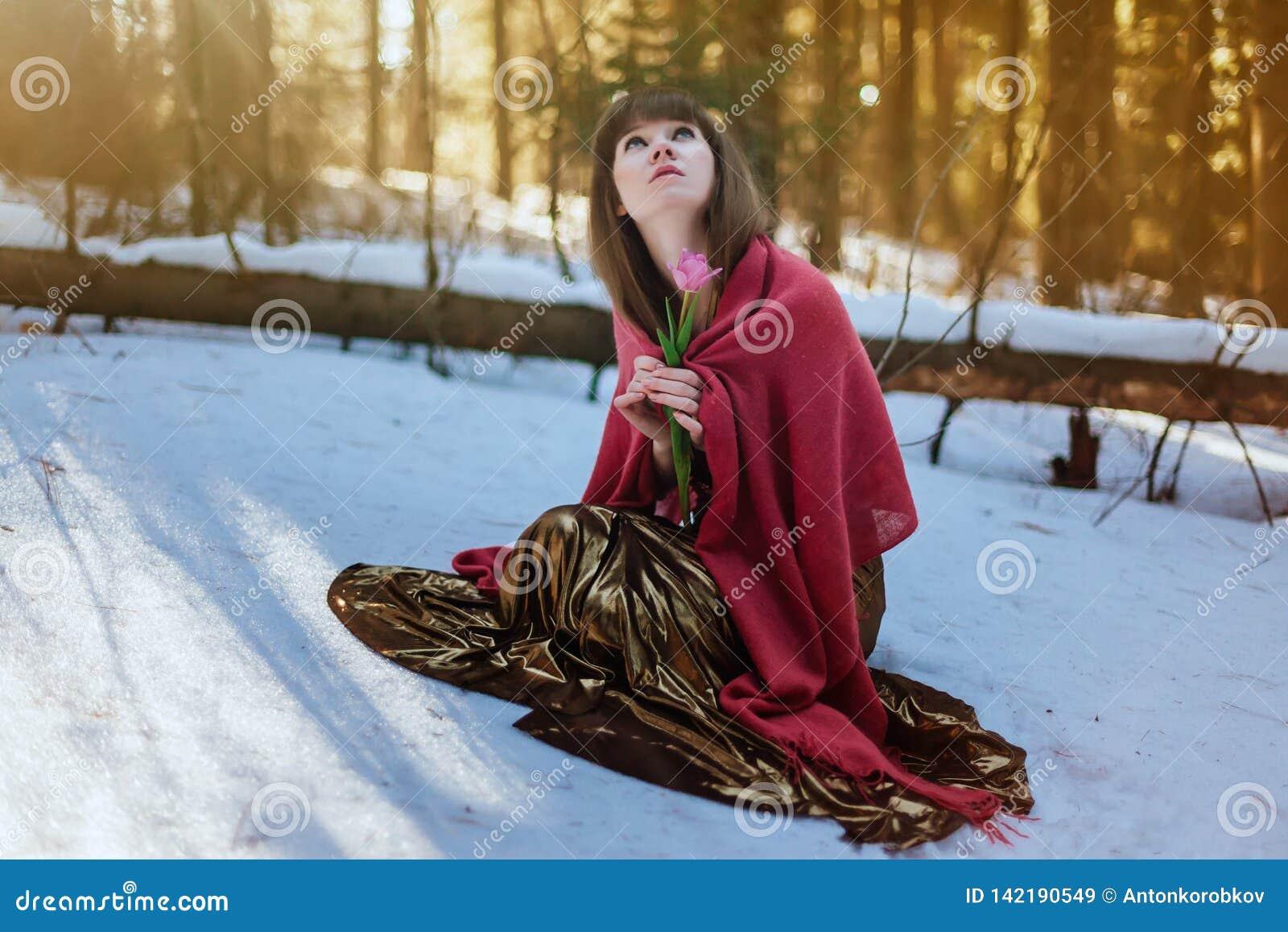 Mooi meisje in Gouden kledingszitting in de sneeuw in de het hout en de aanrakingentulp van de de lentezon