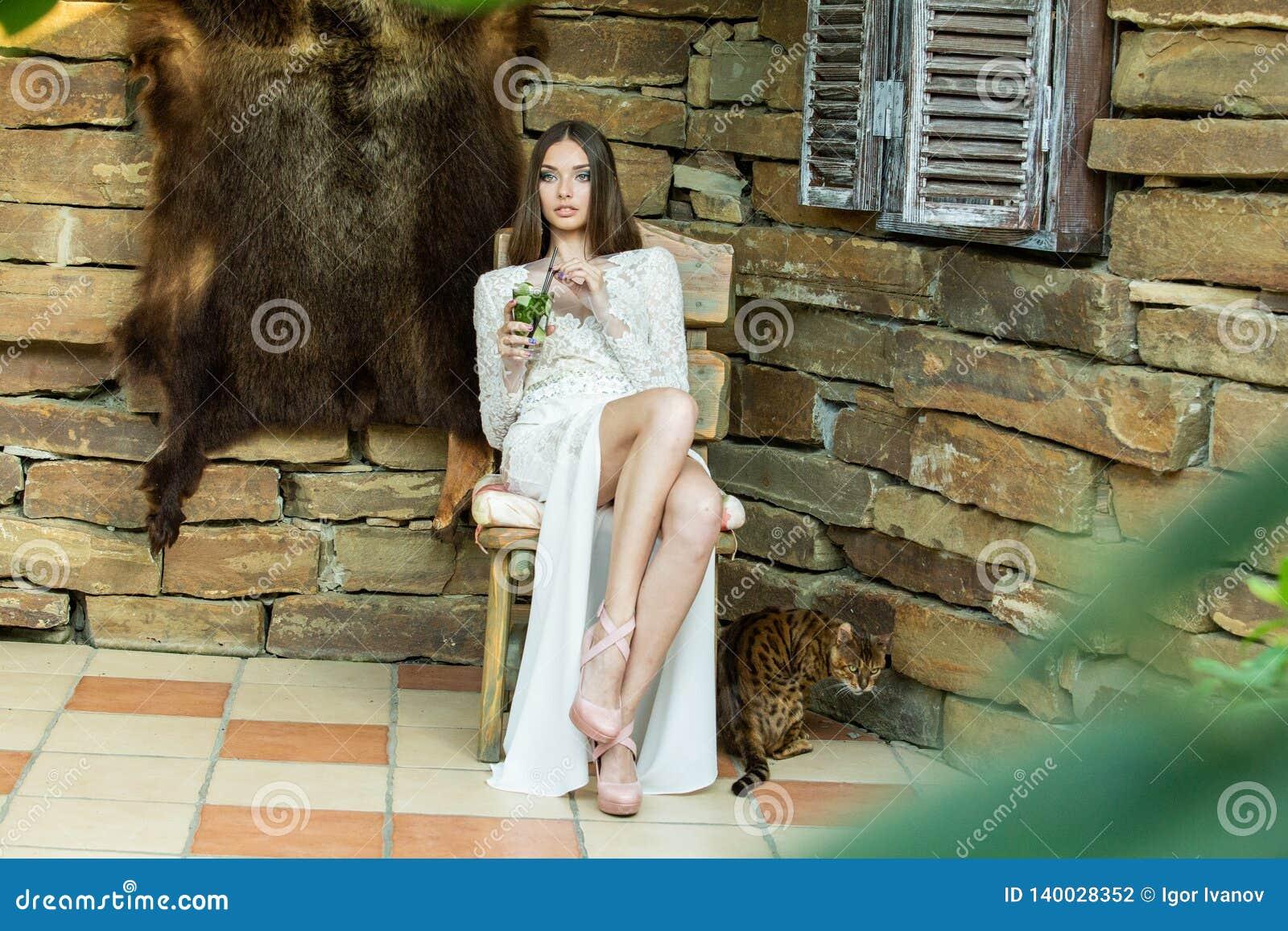 Mooi meisje in het witte kleding stellen met een glas van mojito in haar handen
