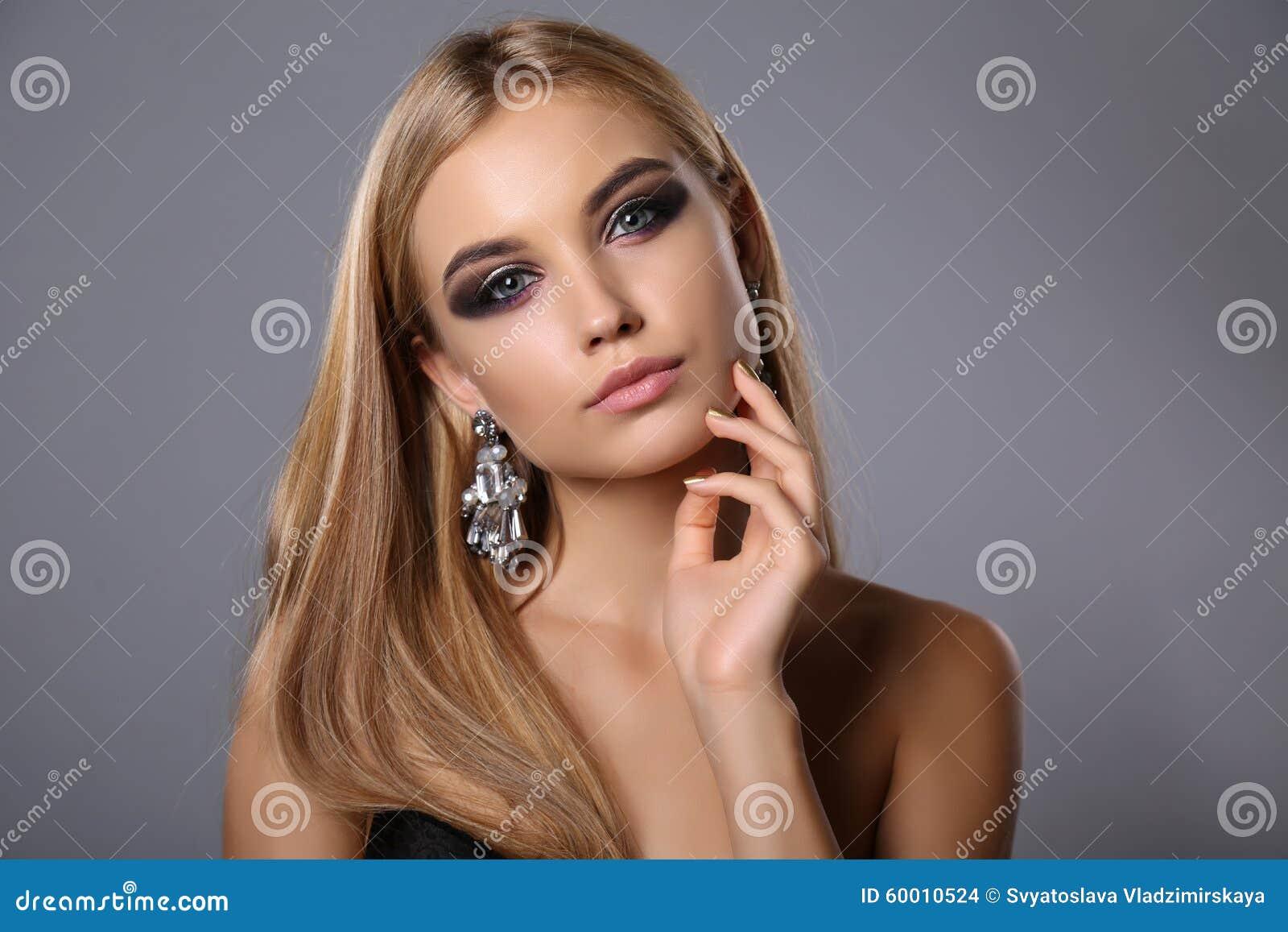 Mooi meisje met blonde haar en avondmake-up met juweel