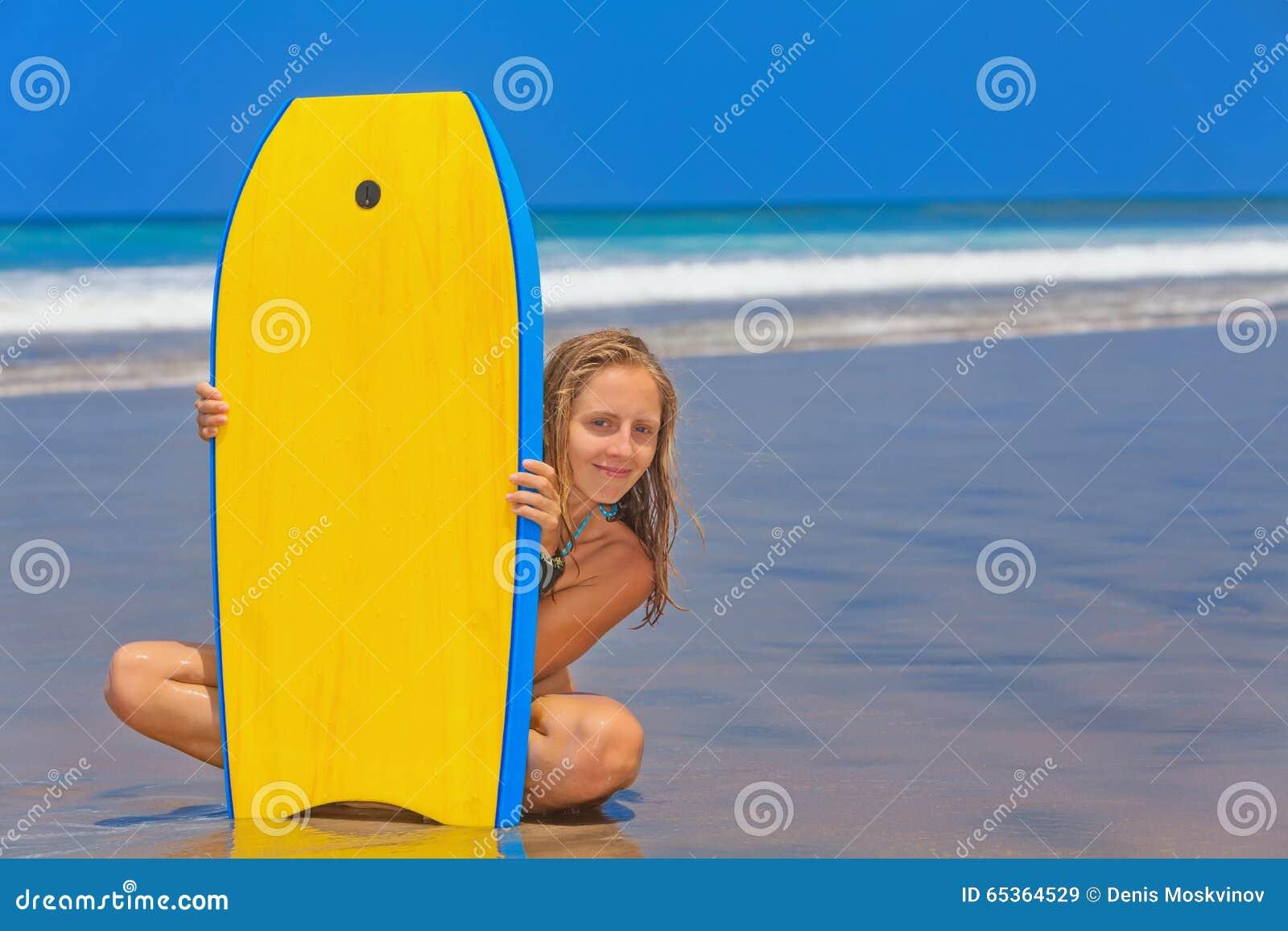 Mooi meisje met brandingsraad op overzees strand met golven