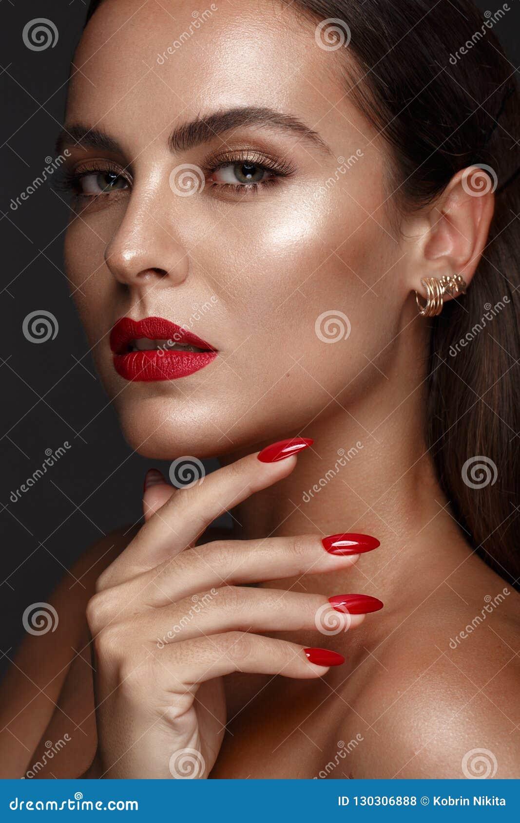 Mooi meisje met een klassieke samenstelling en rode spijkers Manicureontwerp Het Gezicht van de schoonheid