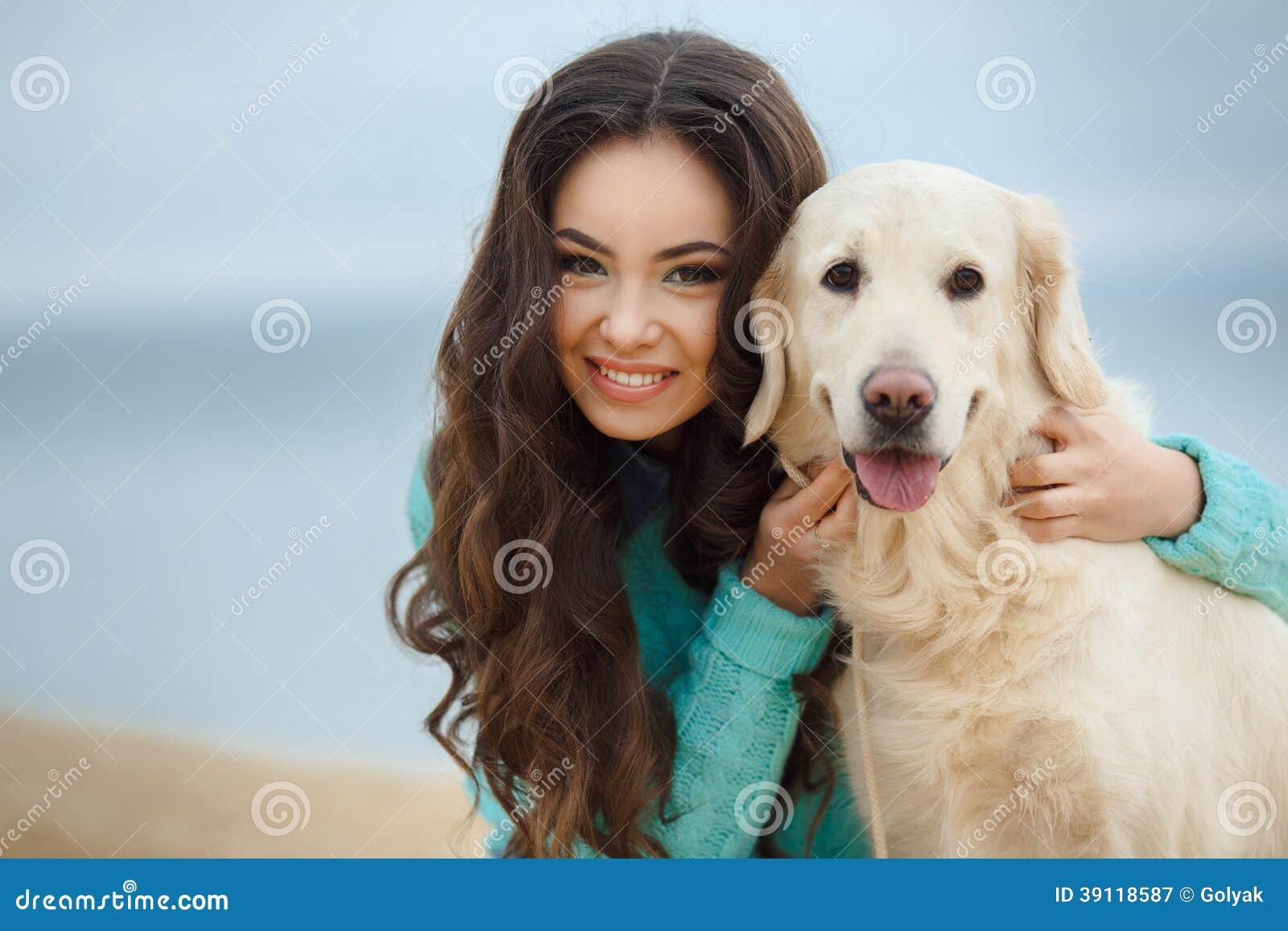 Mooi meisje met haar hond dichtbij overzees