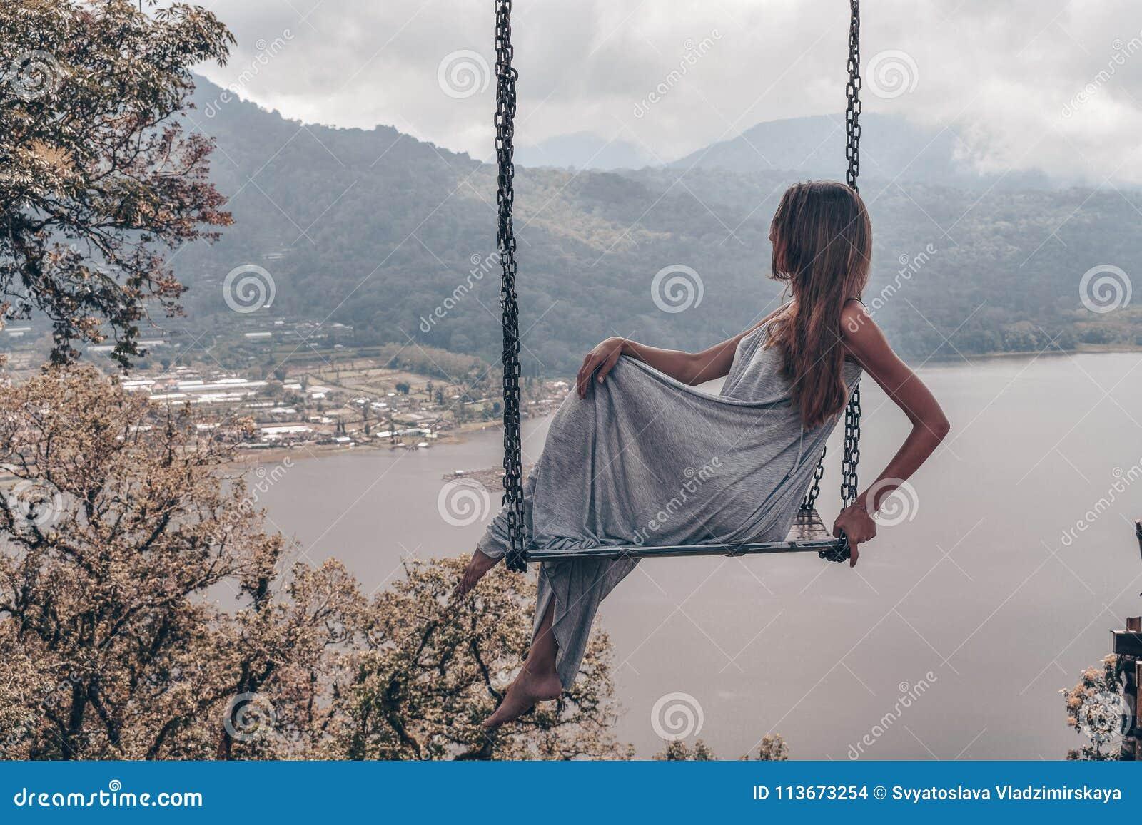 Mooi meisje met lang donker haar in het elegante grijze kleding stellen