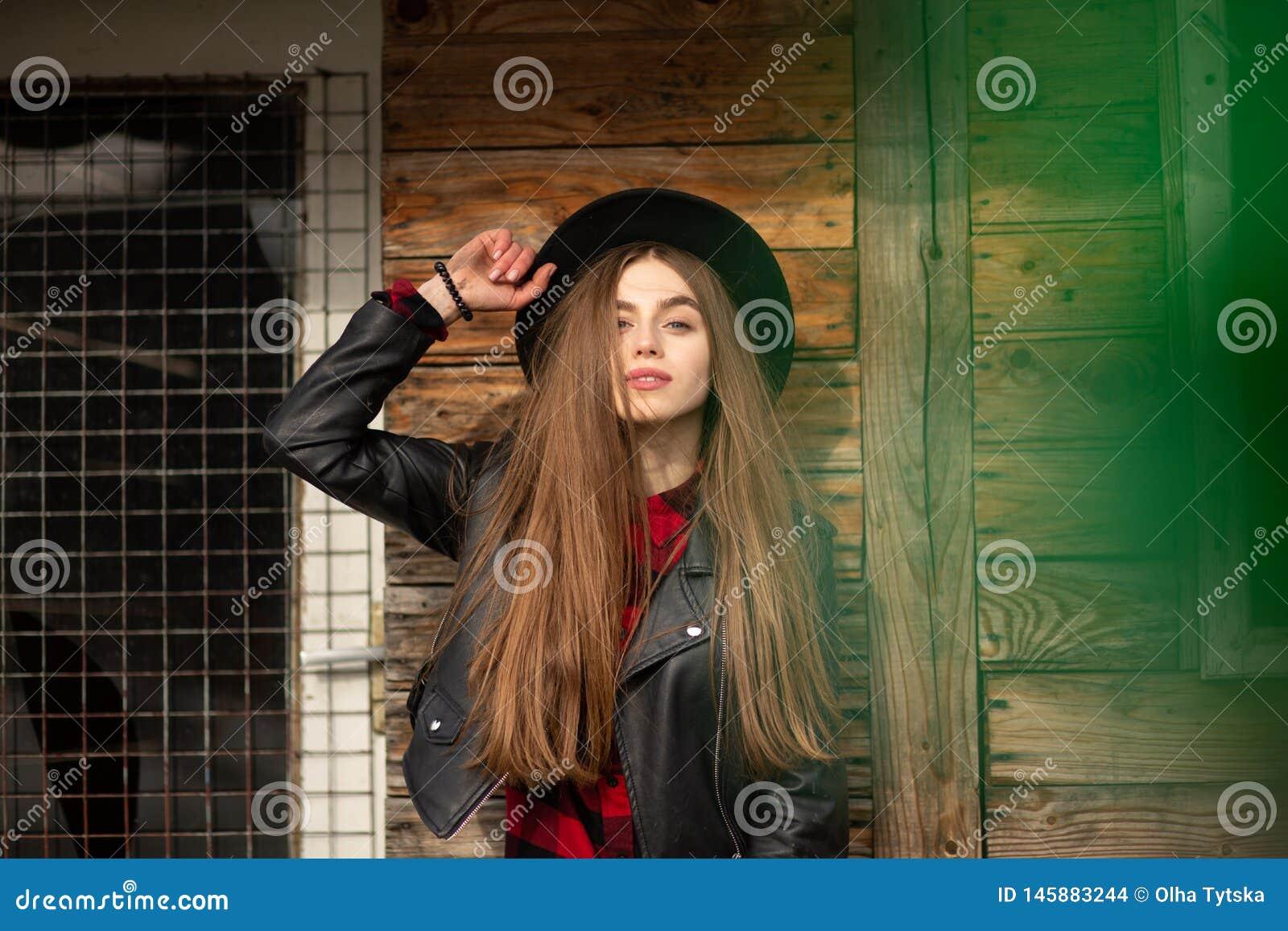 Mooi meisje met lang haar en zwarte hoed, tribunes op de achtergrond van uitstekend oud blokhuis