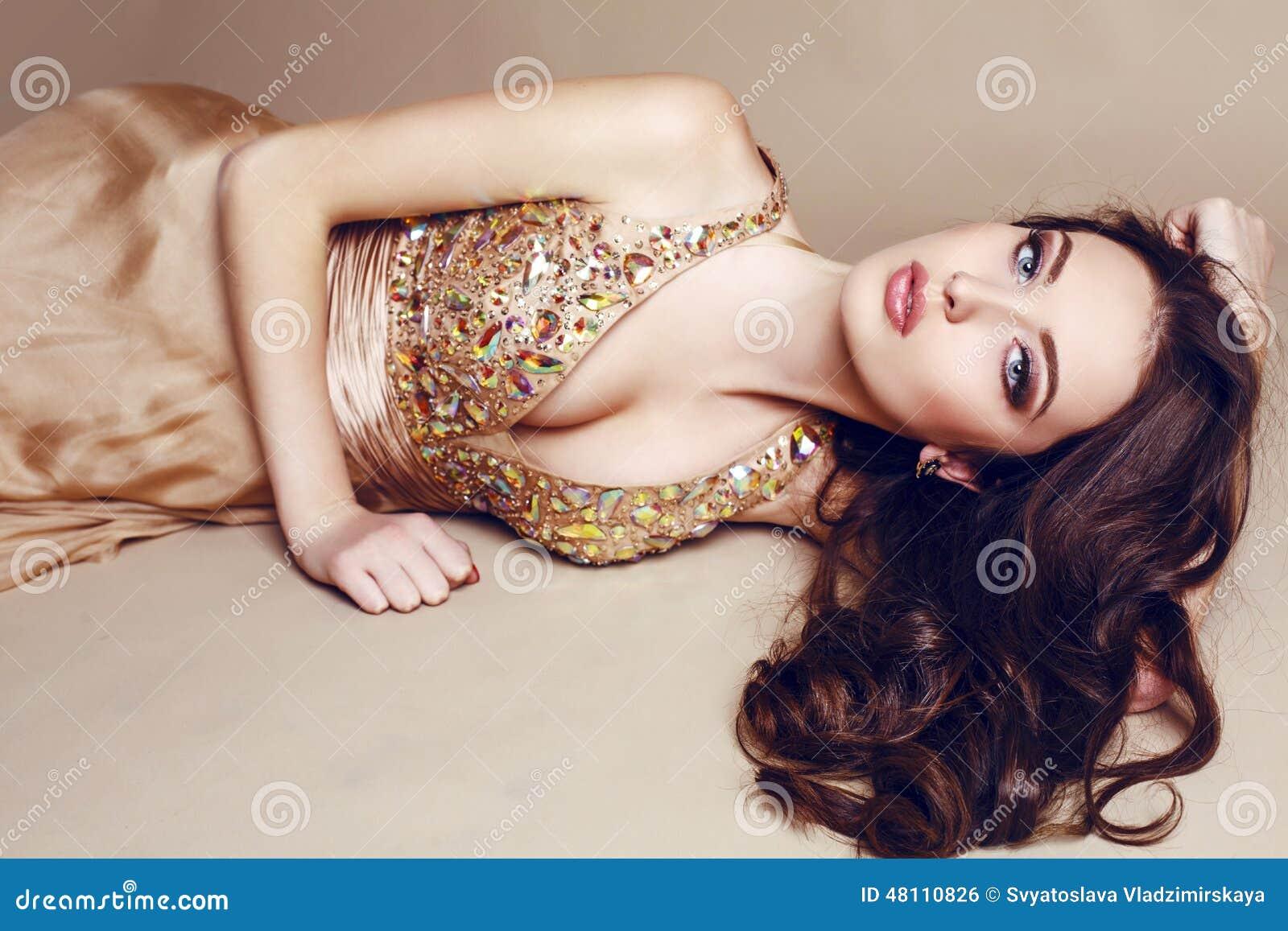 Mooi meisje met luxueus donker haar in lovertjekleding het stellen bij studio