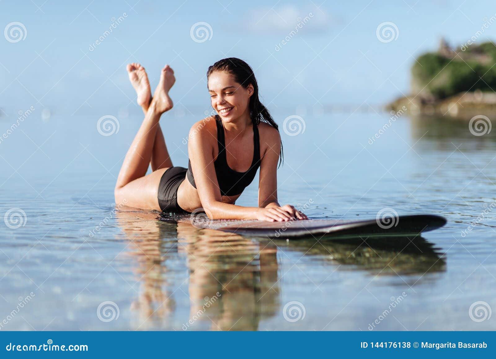 Mooi meisje op een brandingsraad in de oceaan