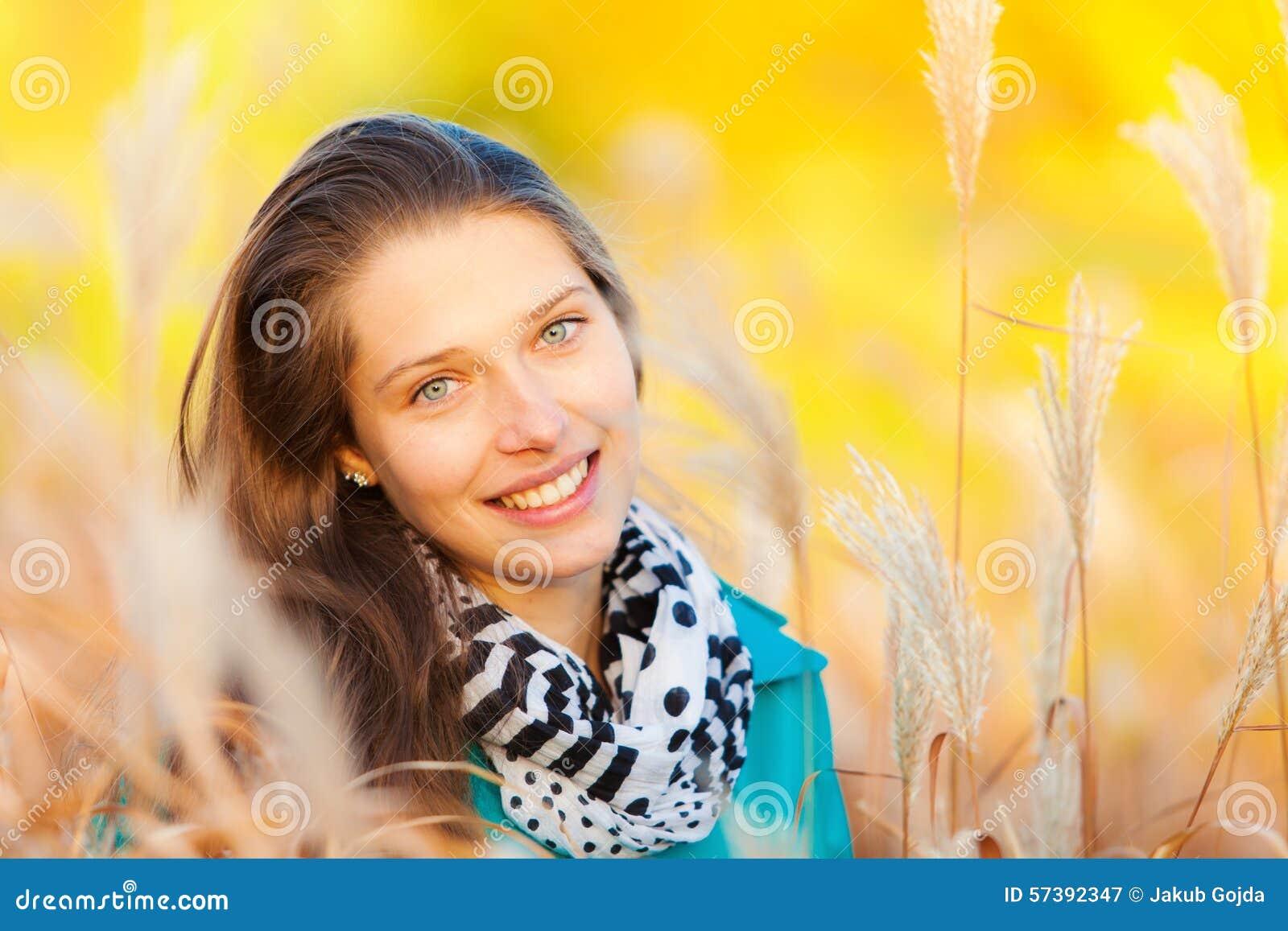 Mooi meisjesportret in de herfstgras