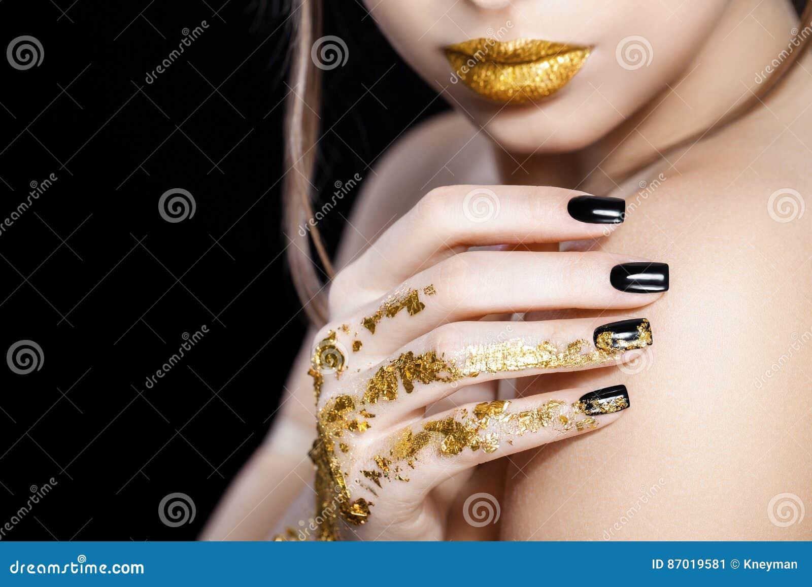 Mooi model het gezichtsportret van de Maniervrouw met gouden lippenstift en zwarte spijkers Glamourmeisje met heldere make-up sch