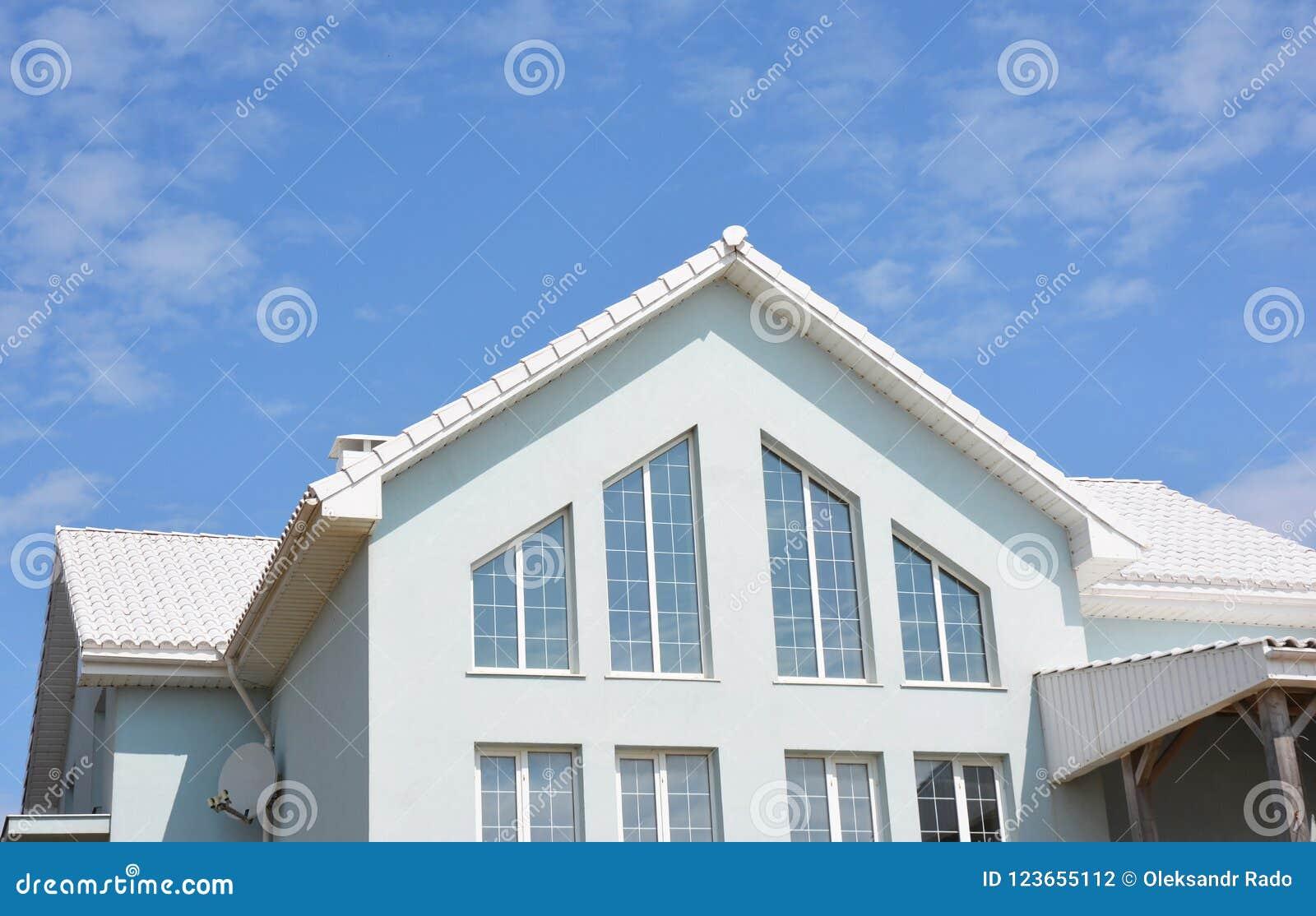 Mooi modern huis met witte muren, witte daktegels en grote panoramische huis zoldervensters