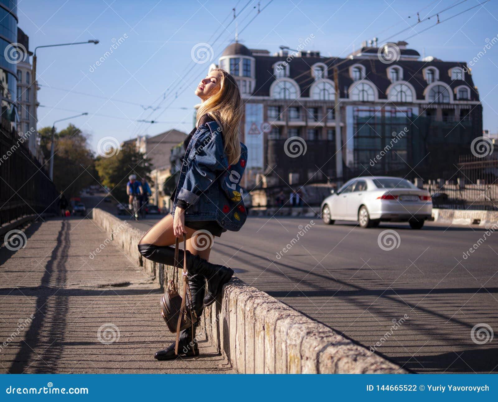 Mooi modieus tienermeisje met stromend haar in de volledige groei op een stadsbrug