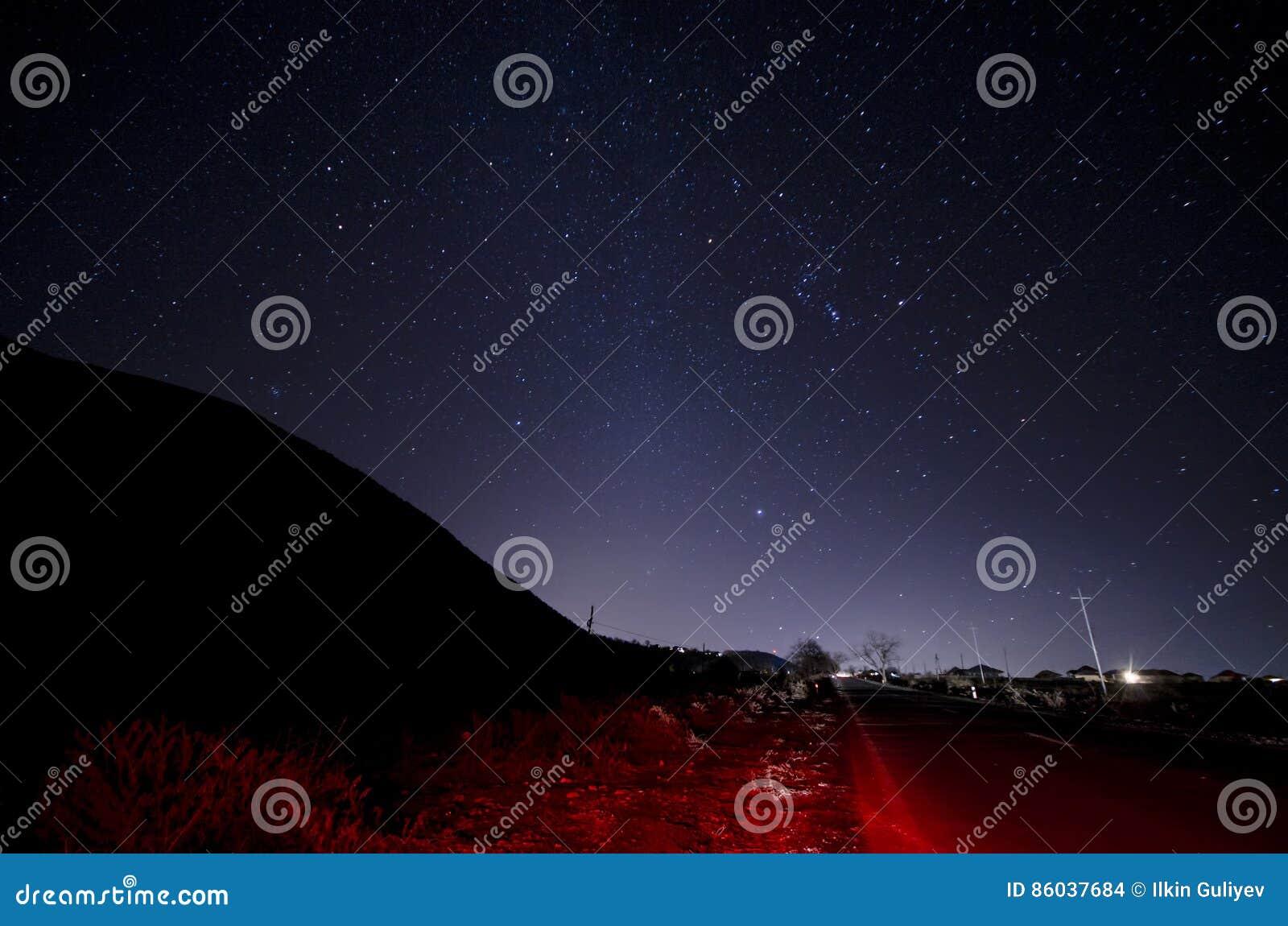 Mooi nachtlandschap van sterren bij hemel en bergsilhouet dichtbij weg met autoslepen Weg in de bergen onder sterrig