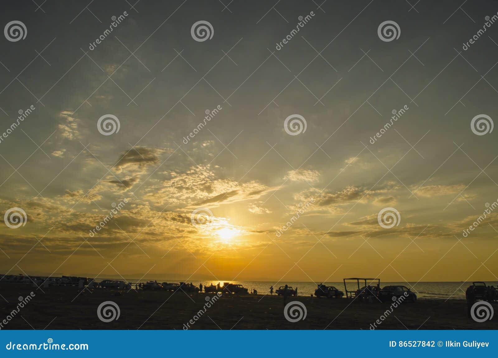 Mooi opvlammend zonsonderganglandschap bij Kaspische overzees en oranje hemel boven het met ontzagwekkende zon gouden bezinning o