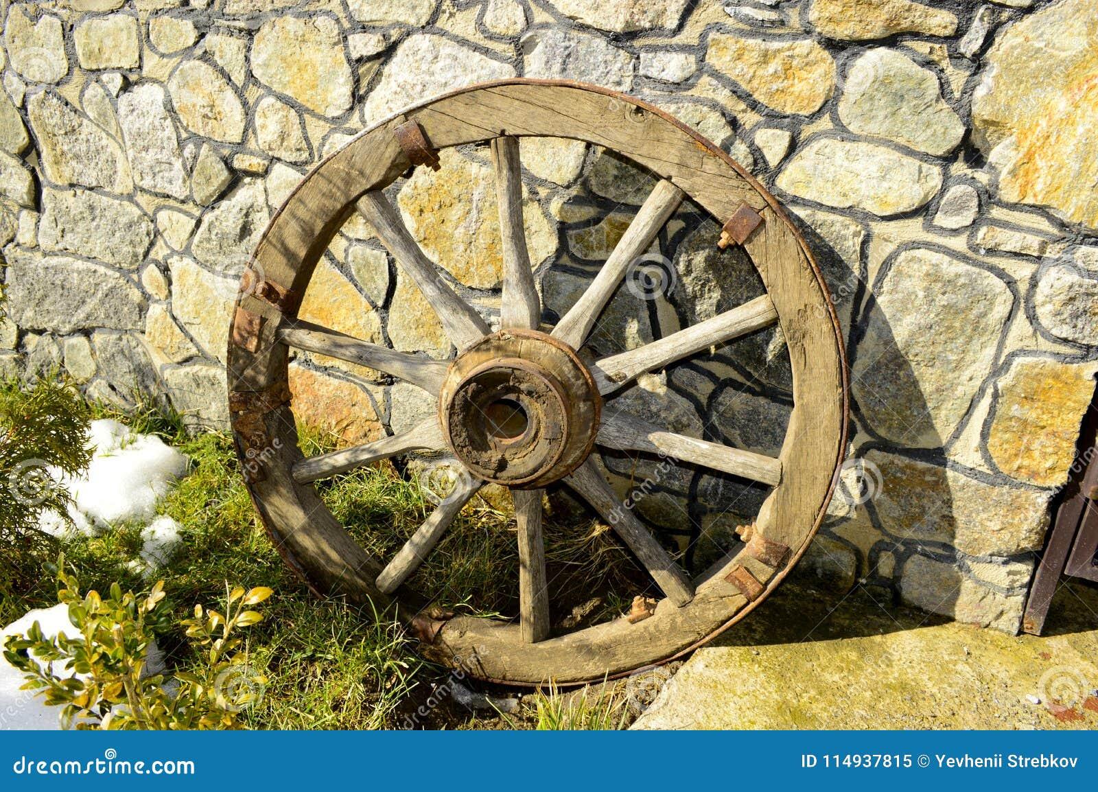 Mooi oud houten wiel dichtbij de muur