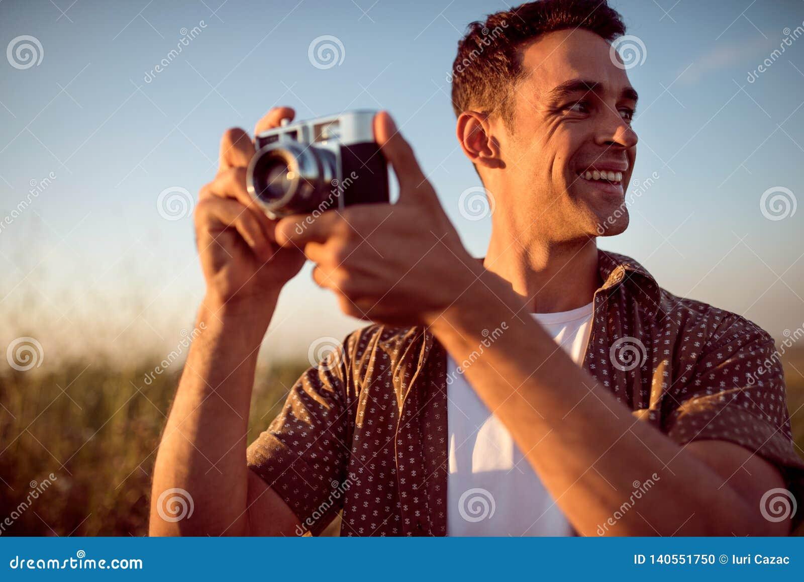Mooi portret van de knappe glimlach jonge mens met uitstekende camera, op een weideachtergrond Reisstemming fotografie