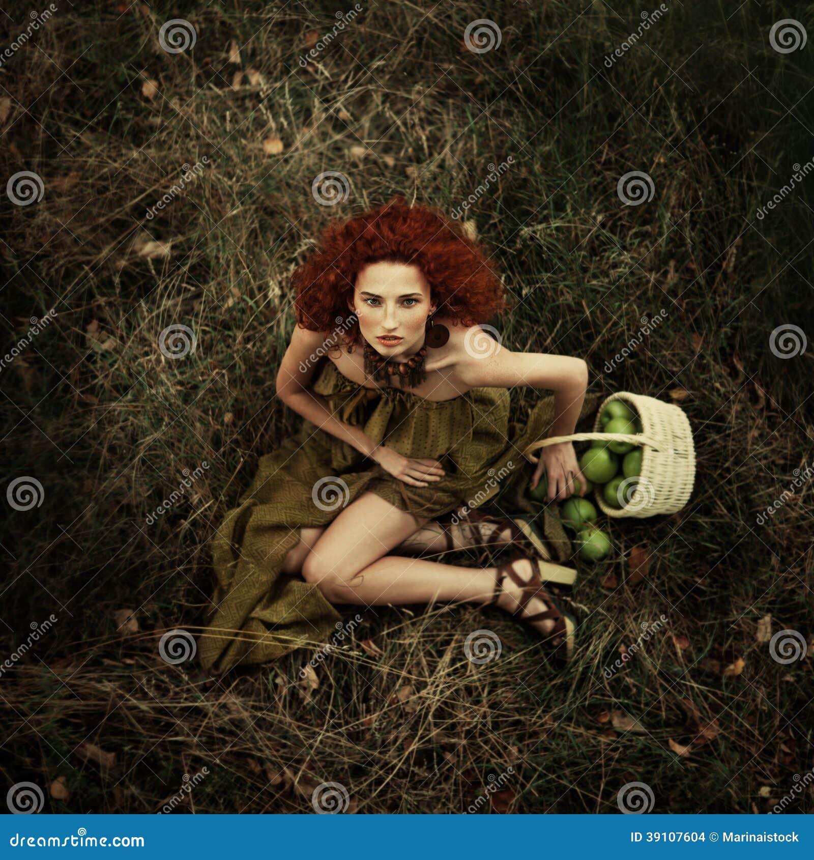 Mooi roodharig meisje in de appelboomgaard