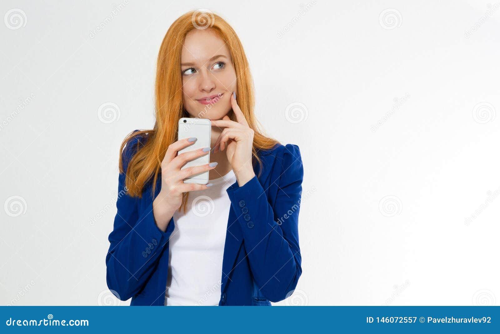Mooi roodharigemeisje met telefoon glimlachen geïsoleerd op witte achtergrond Het jonge foxy wijfje in bedrijfsuitrusting, heeft