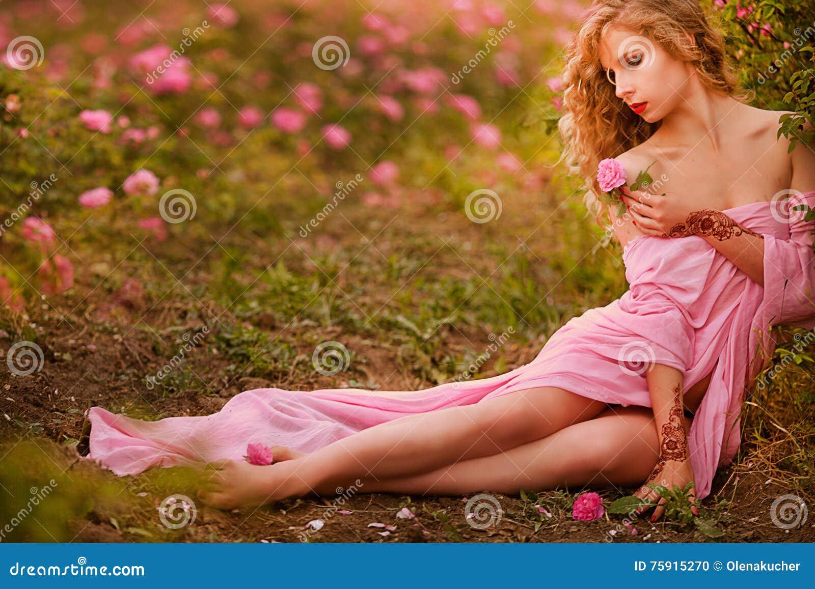 Mooi sexy meisje in een roze kleding die zich in de tuinrozen bevinden