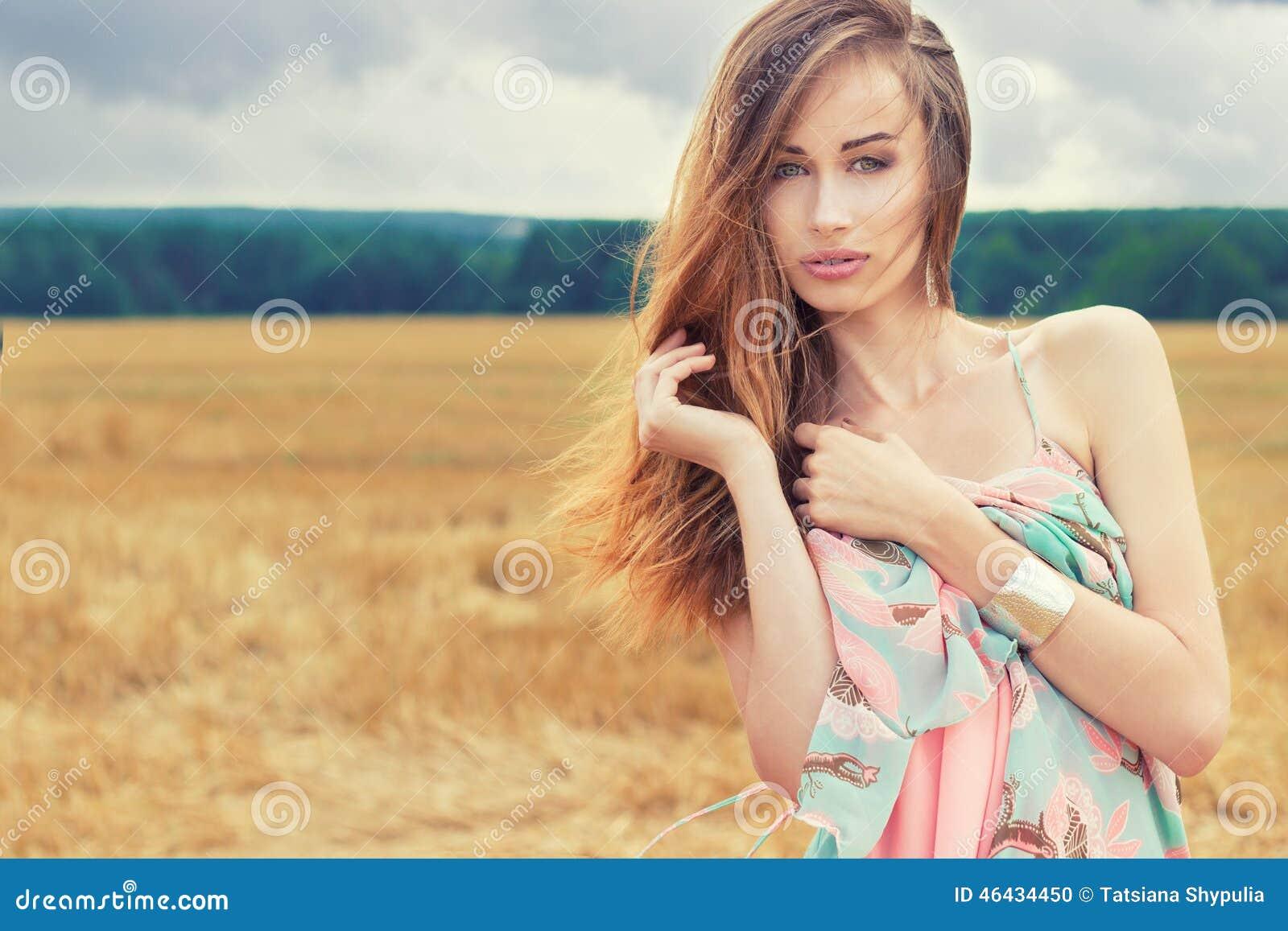 Mooi sexy romantisch meisje met rood haar die een gekleurde kleding, de wind dragen die zich op het gebied op een bewolkte de zom